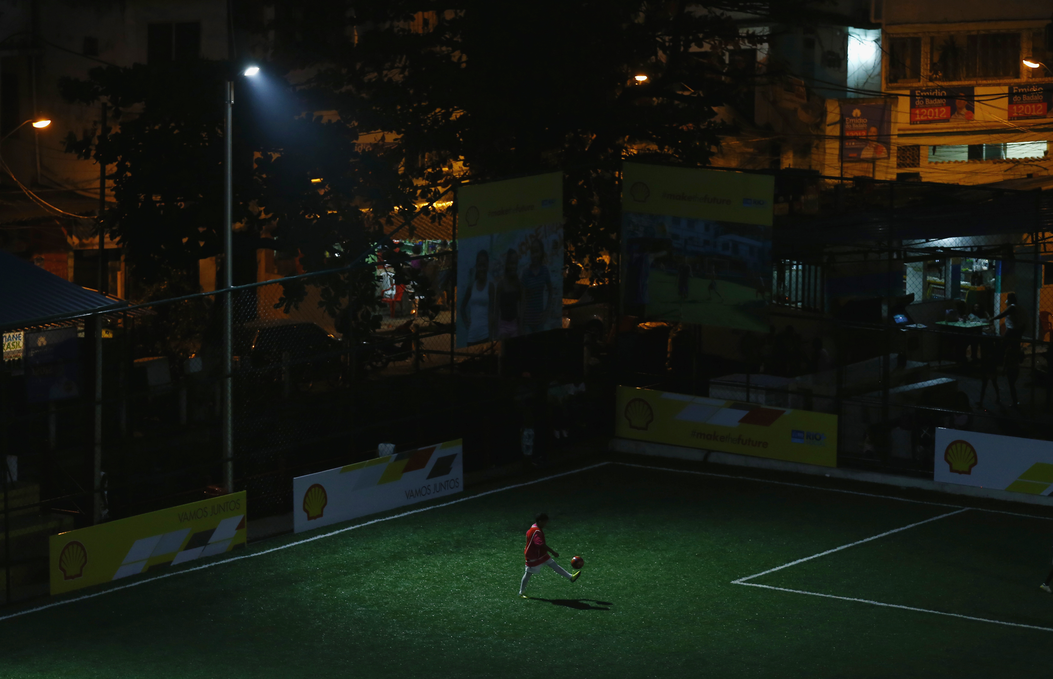 A child plays with soccer ball at a refurbished soccer field at the Mineira slum in Rio de Janeiro September 10, 2014.