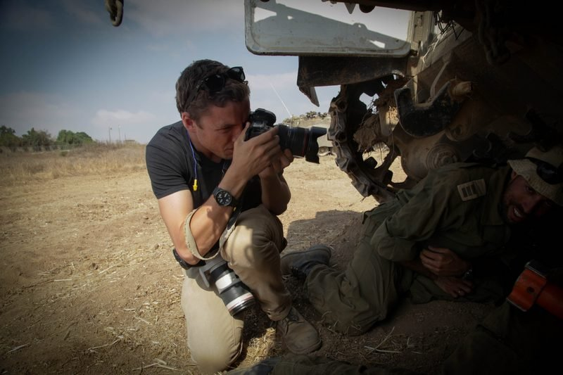 Andrew Burton photographing Israeli soldiers responding to a missile siren near Kfar Aza, Israel, July 23, 2014.