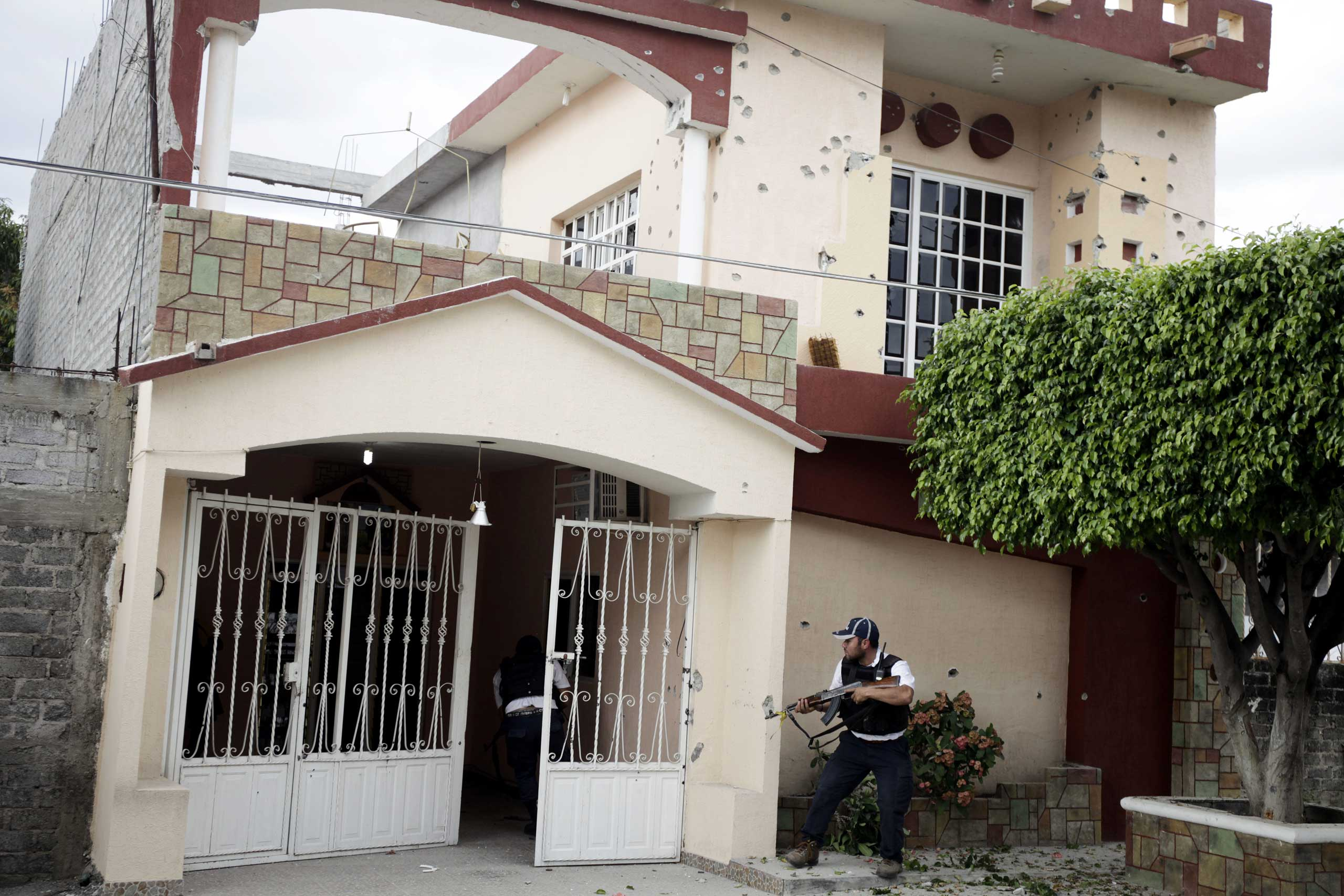 Jan. 12, 2014. Vigilantes enter a house where a sniper for the Knights Templar cartel had been shooting from during a three-hour gunfight in downtown Nueva Italia, Michoac‡n.