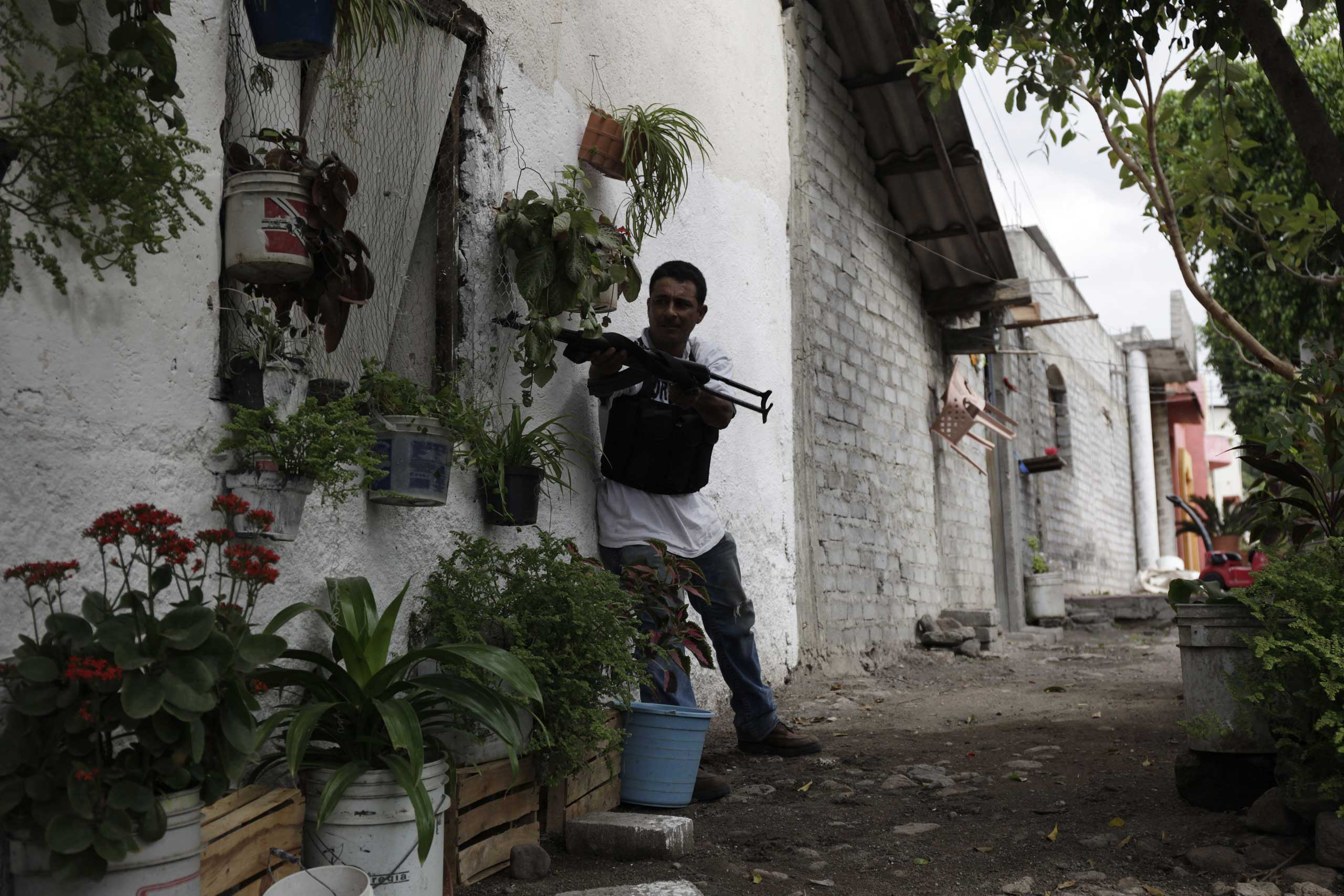 Jan. 12, 2014. A three-hour gunfight between vigilantes and the Knights Templar cartel continues in downtown Nueva Italia, Michoac‡n, Mexico.