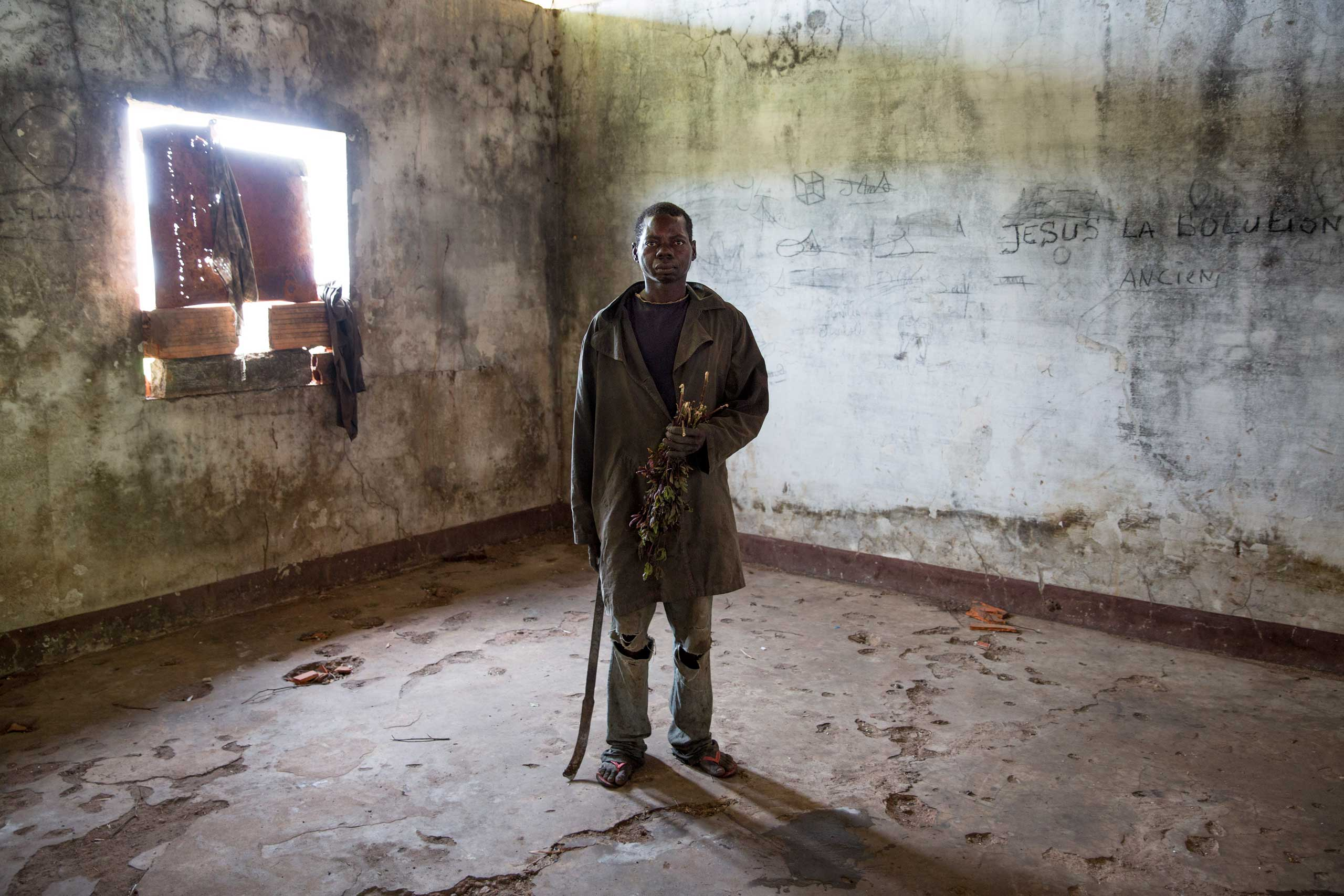 Feb. 2, 2014: A man poses in former Emperor Jean-Bédel Bokassa's compound near the village of Pissa. He is one of the many Christians there, originally recruited by Séléka to become soldiers, but later abandoned by their leader. No food is available so they hunt rats to eat, fearing to leave as they could be considered Séléka collaborators.