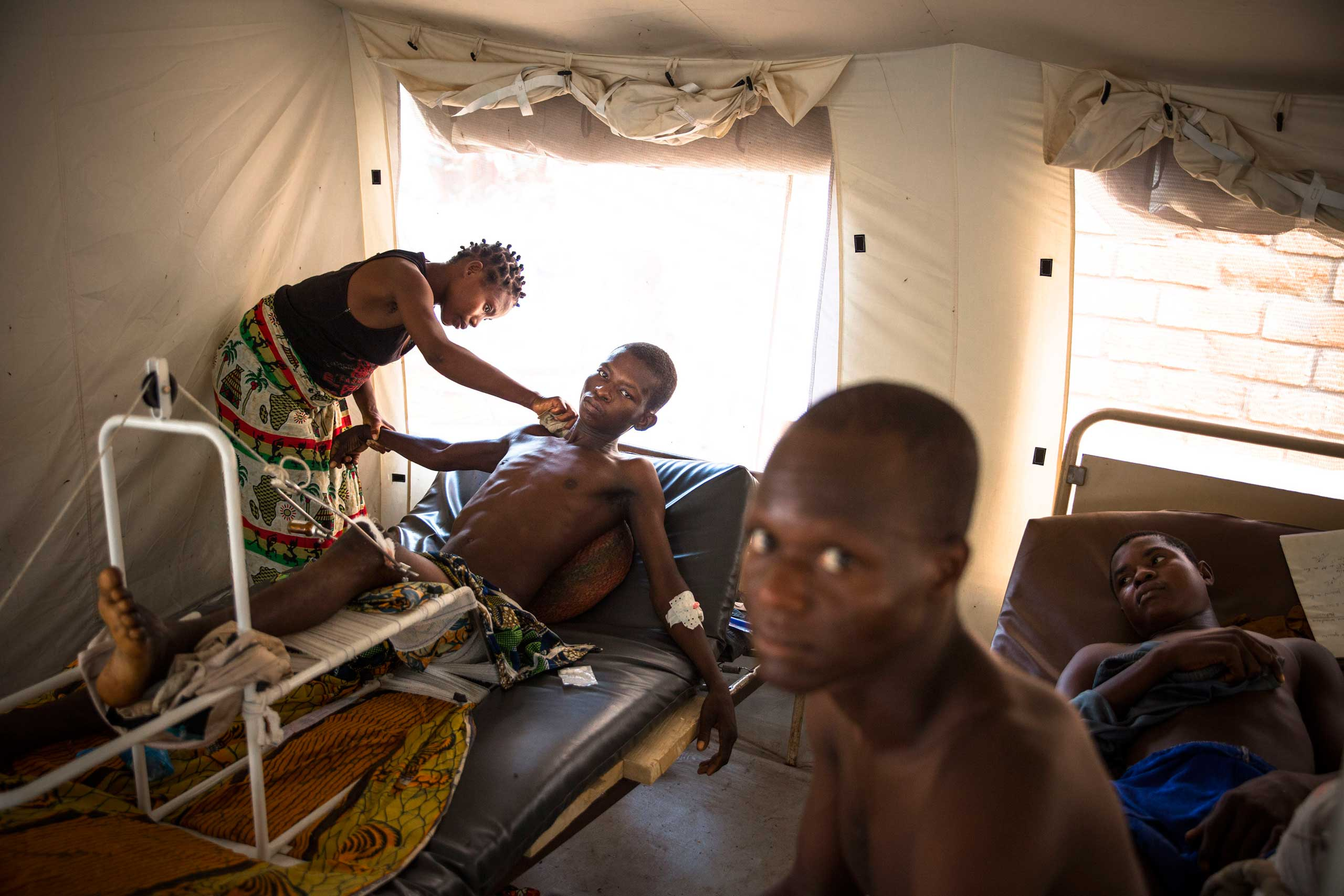 Jan. 31, 2014: A man wounded during previous days of fighting between Christians and Muslims is washed by his wife in a tent in Bangui's community hospital.