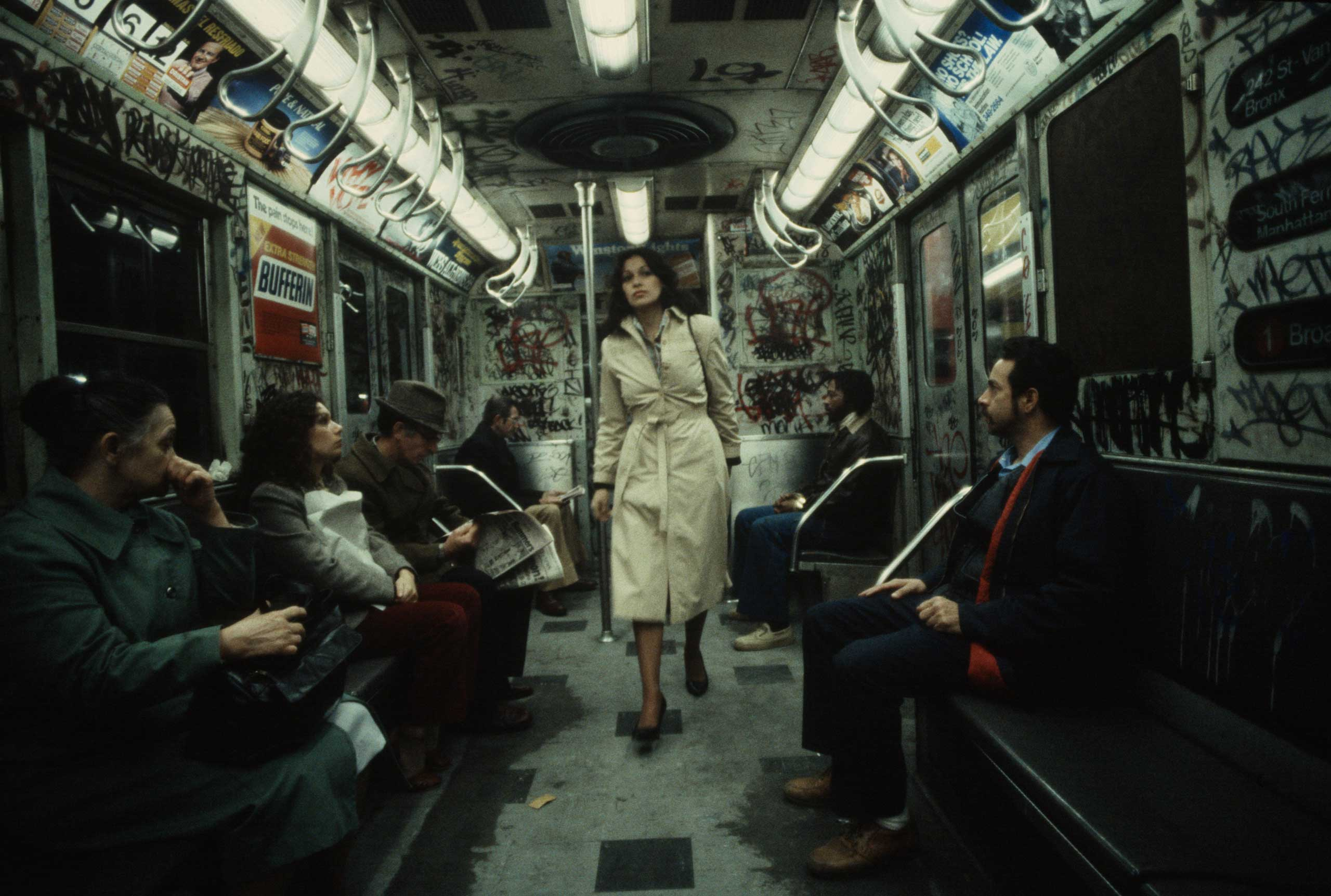 The following previously unpublished photos were taken by Christopher Morris in 1981: A woman walks through a heavily graffitied subway car, 1981.