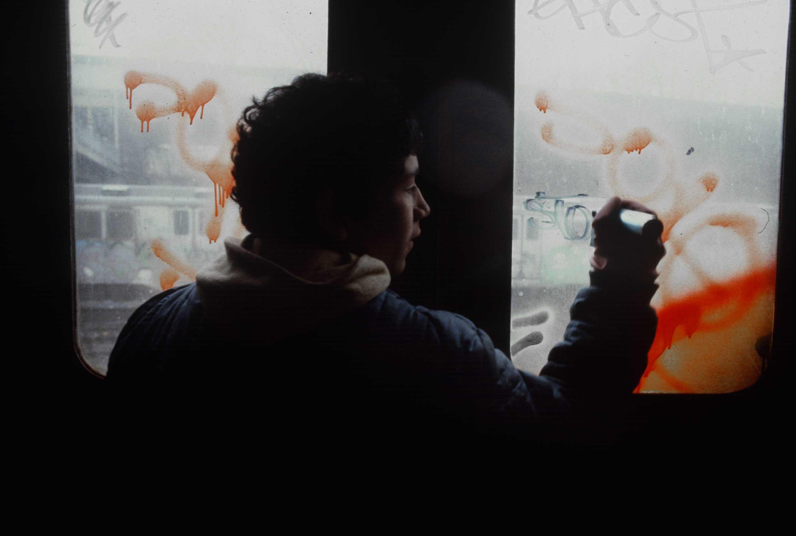A young teen tags a D train subway car window in a South Bronx train yard, 1981.
