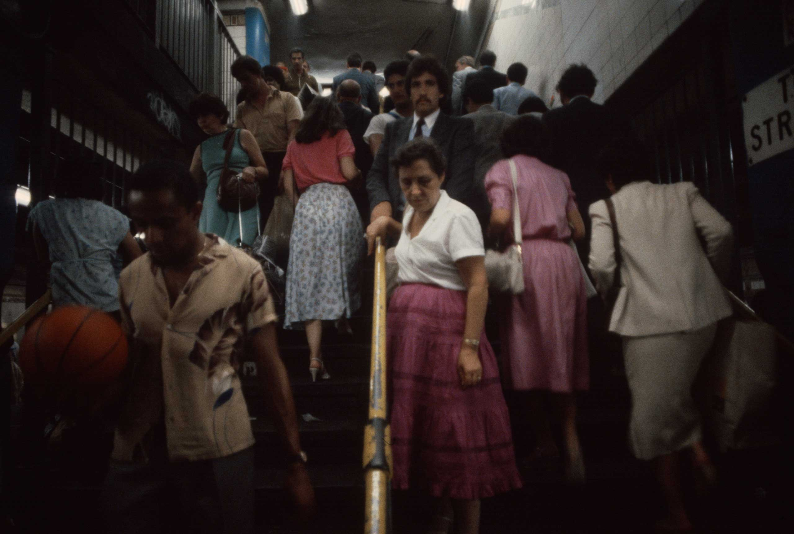 Commuters ascend and descend stairwells during rush hour, 1981.