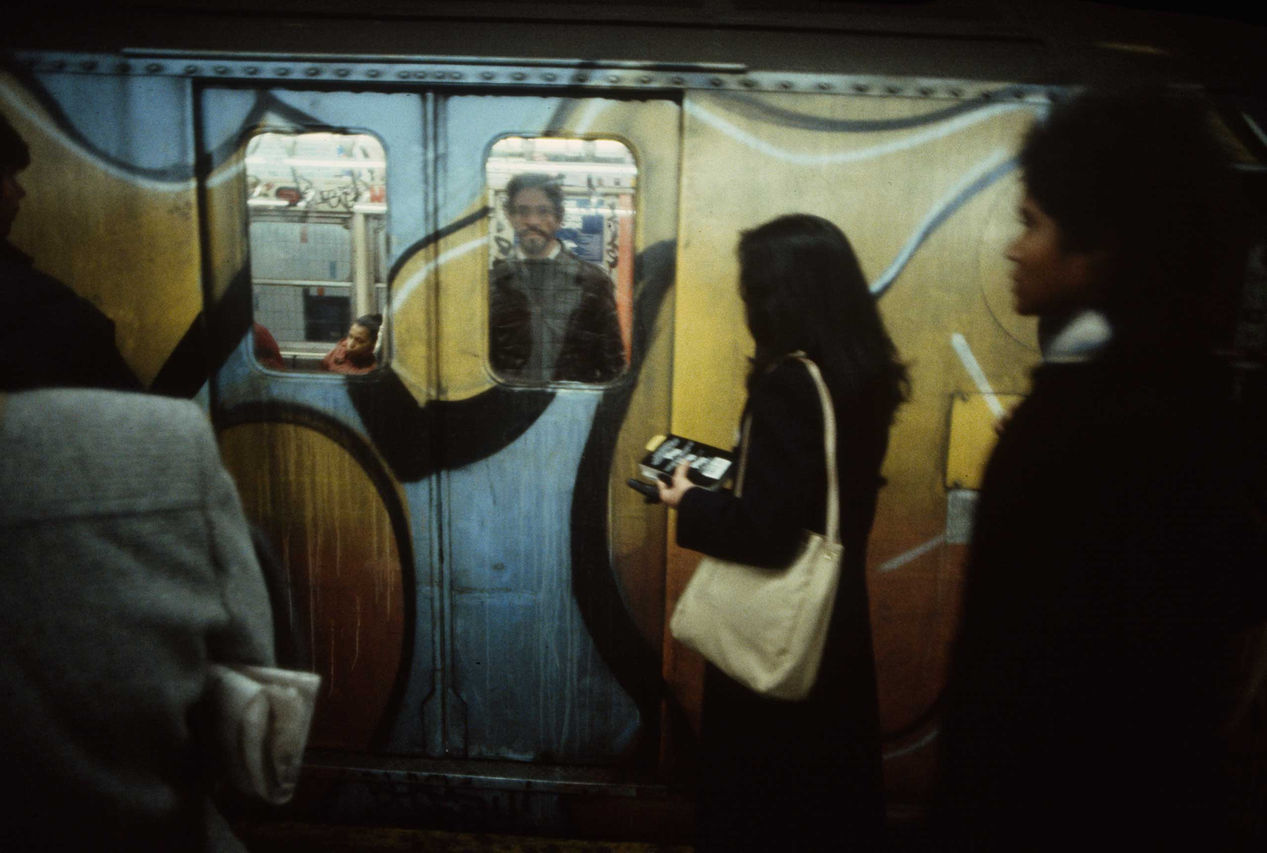 A woman waits to board a train pulling into a station, 1981. Graffiti on the outside of subway cars was usually more elaborate than that inside.