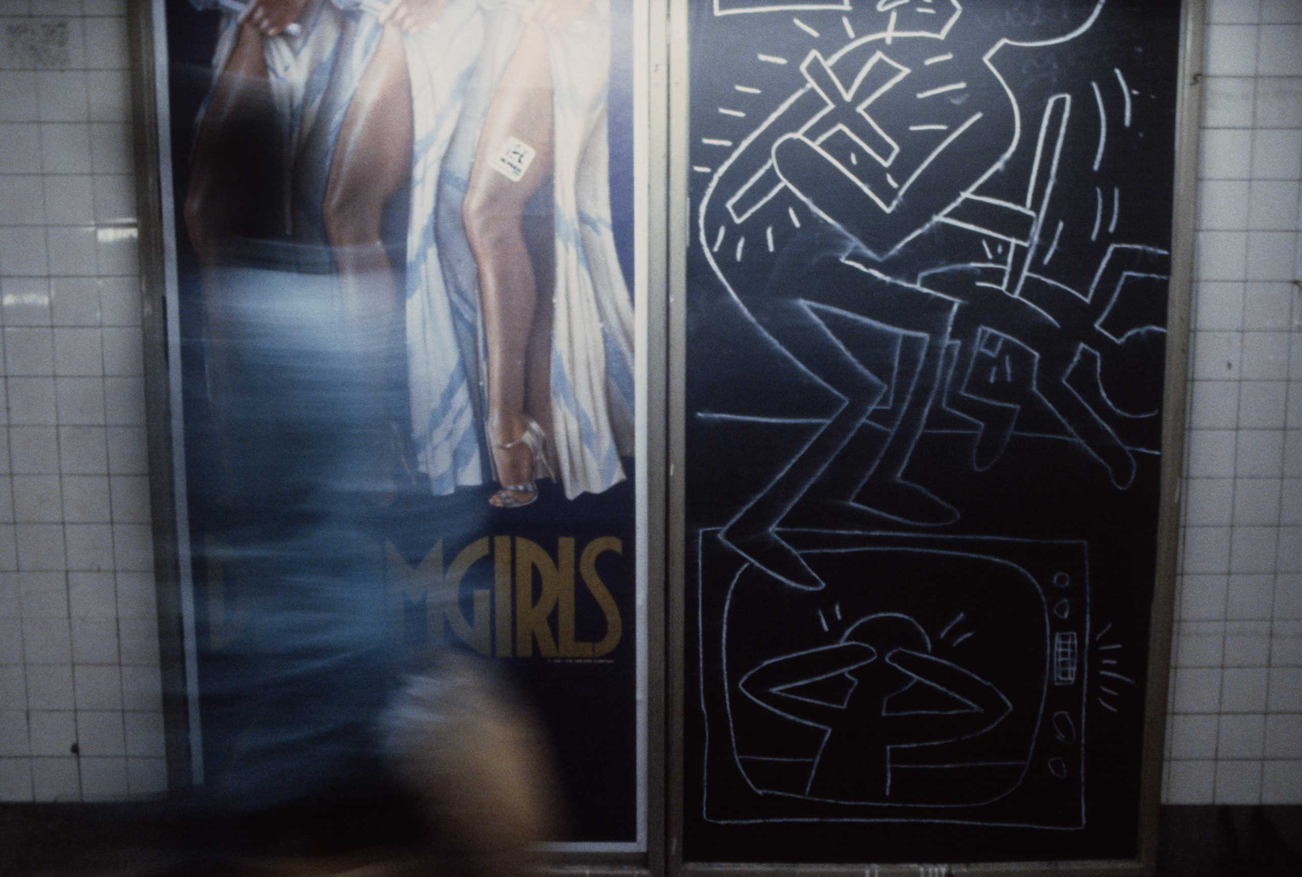A commuter walks by a poster for the musical Dreamgirls and a Keith Haring chalk drawing, 1981.