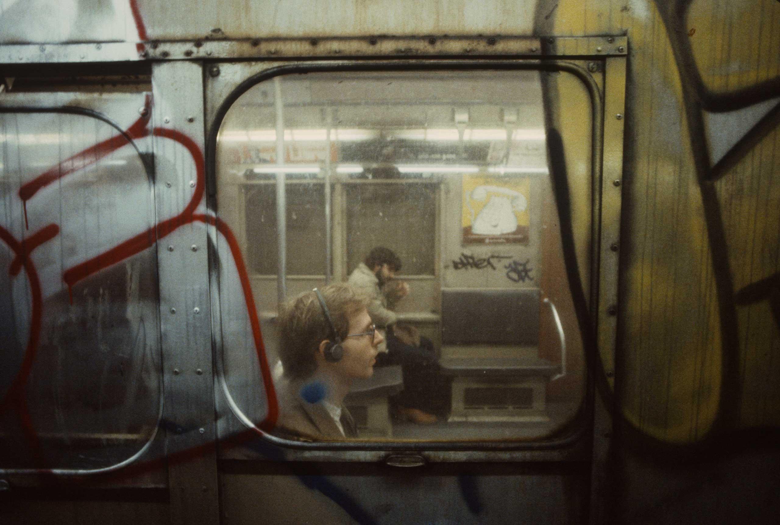 A man is seen wearing headphones through a subway car window, 1981.