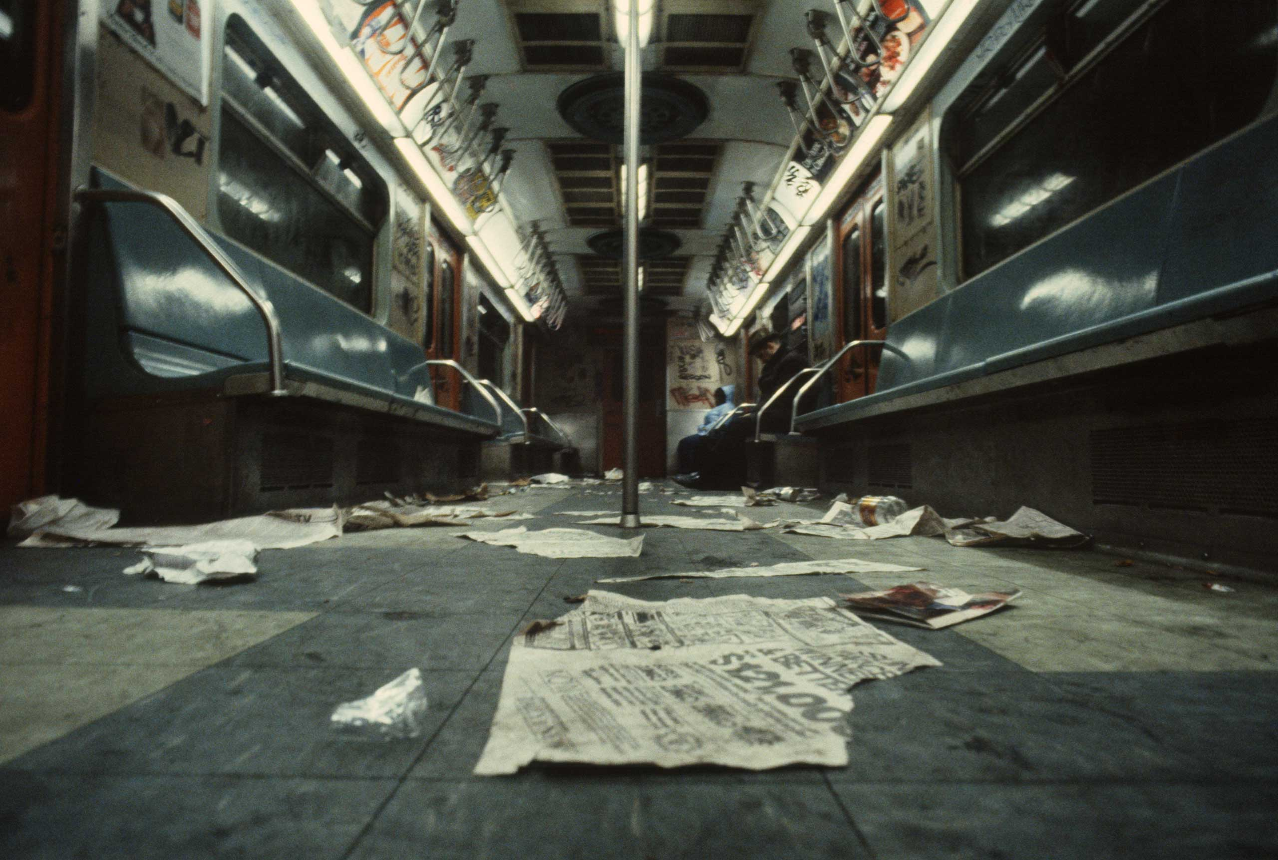 Discarded newspapers and trash on the floor of a subway car, 1981.