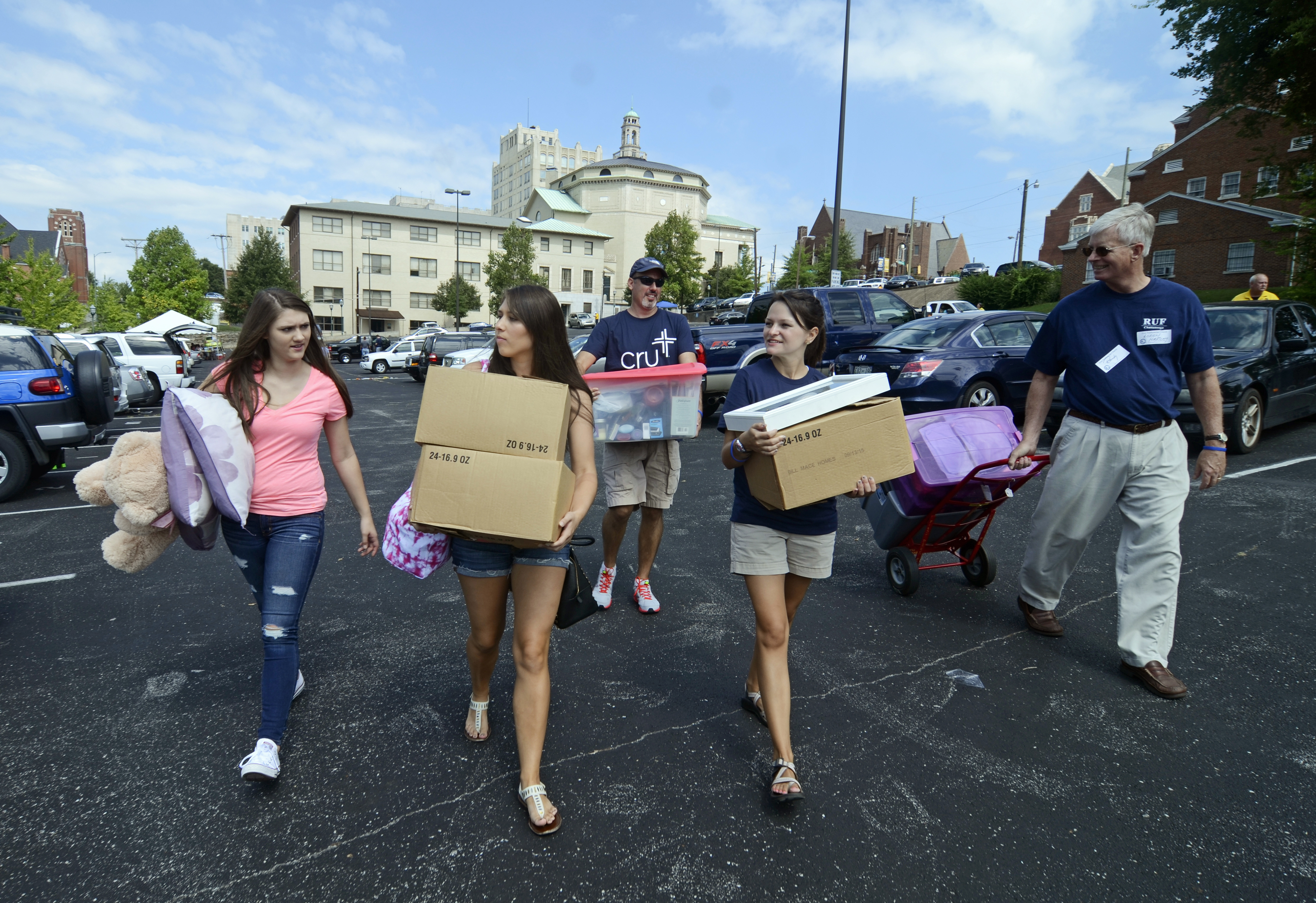 Chloe Bradley, left front, and Logan Laney, right front, help Tori Bradley, middle front, move into campus housing on Aug. 14, 2014,  at the University of Tennessee at Chattanooga in Chattanooga, Tenn.