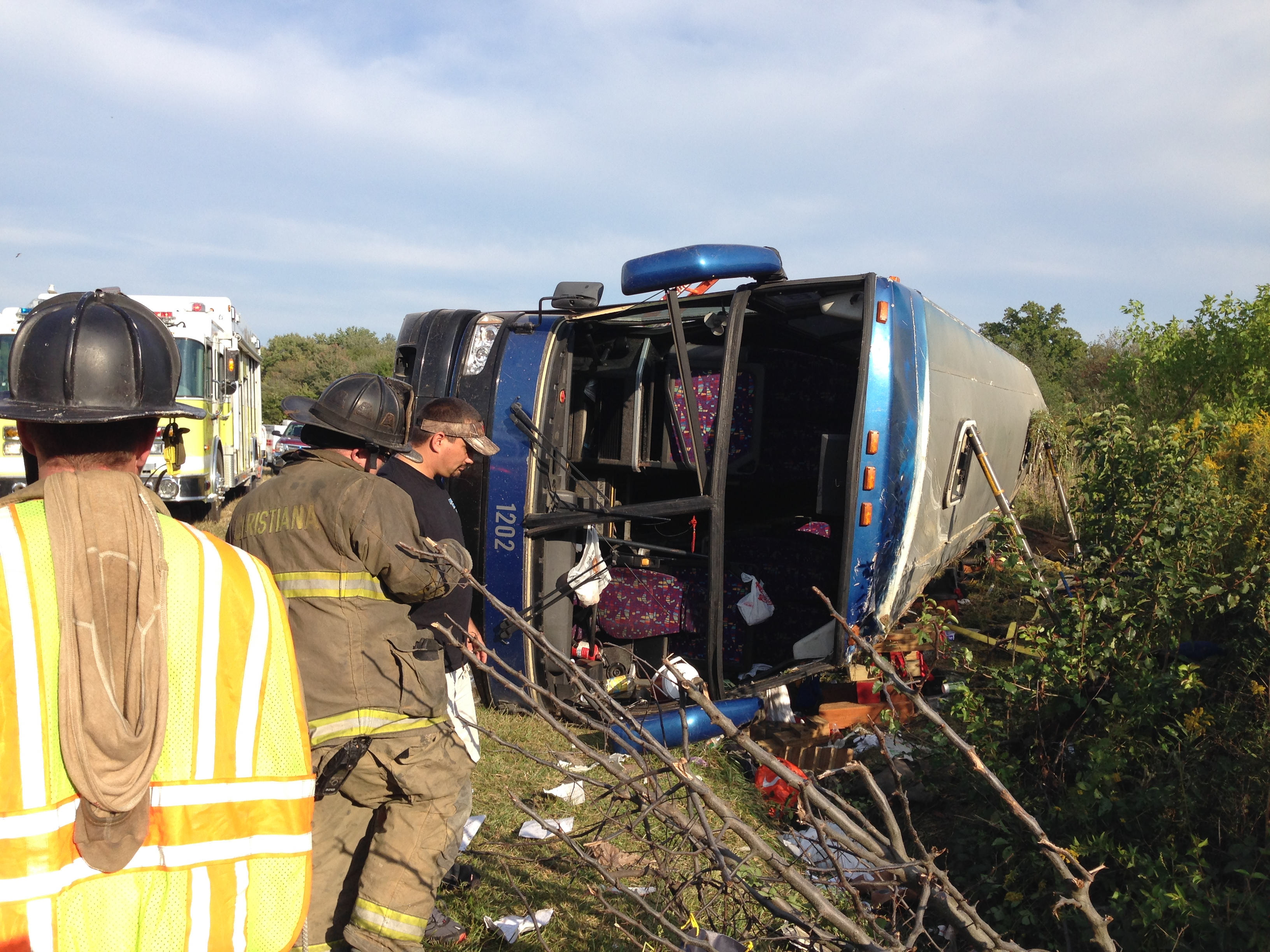 Passengers from a tour bus are treated for injuries near the overturned bus at the Tybouts Corner on ramp from southbound Del. 1 to Red Lion Road in Bear, Del. on Sept. 21, 2014.