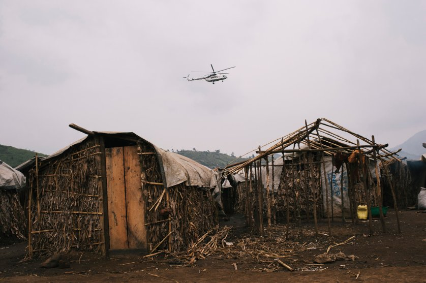 A United Nations helicopter flies over make-shift house in a camp for internally displaced persons in the town of Nyabiondo, July 21, 2014.