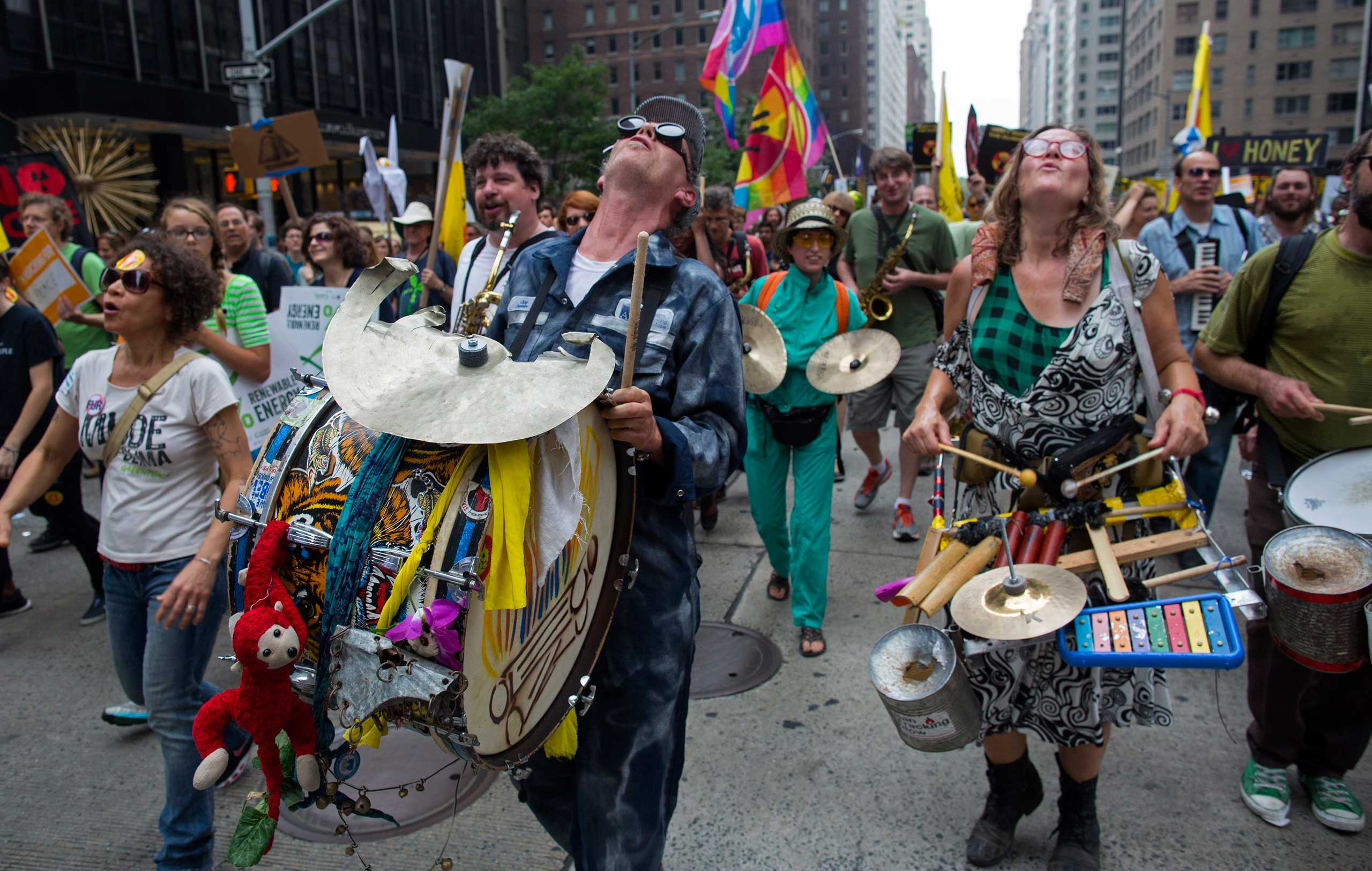 Marchers sing out as they walk along Sixth Ave. during the People's Climate March in New York, Sept. 21, 2014.