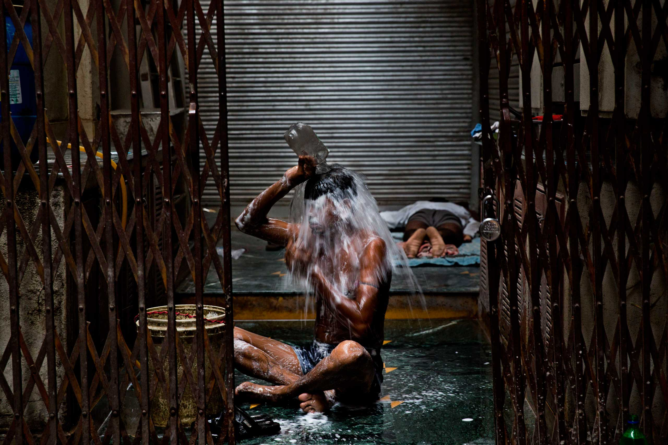 Sept. 22, 2014. An Indian homeless man takes a morning bath in the old city area of New Delhi, India.