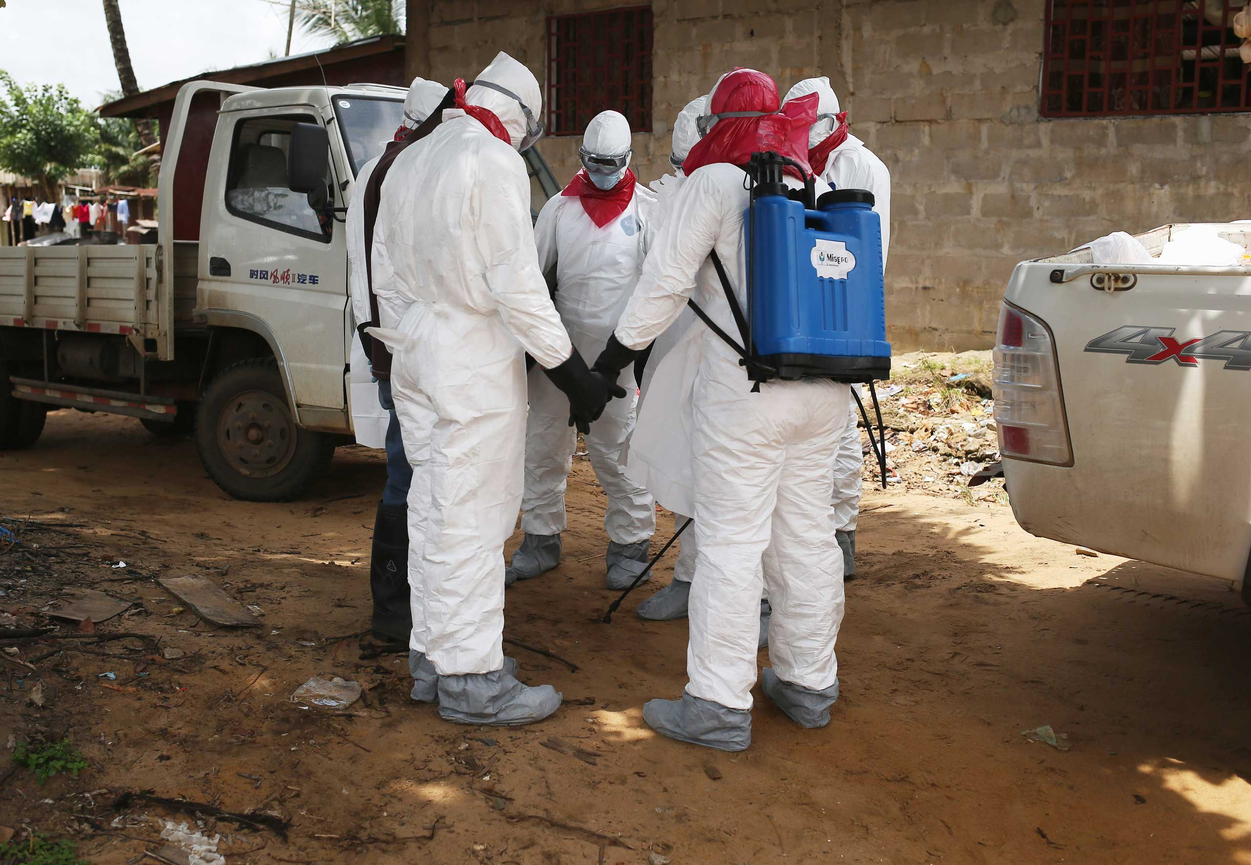 A burial team from the Liberian health department prays before entering a house to remove the body of a woman suspected of dying of the Ebola virus on Aug. 14, 2014 in Monrovia.