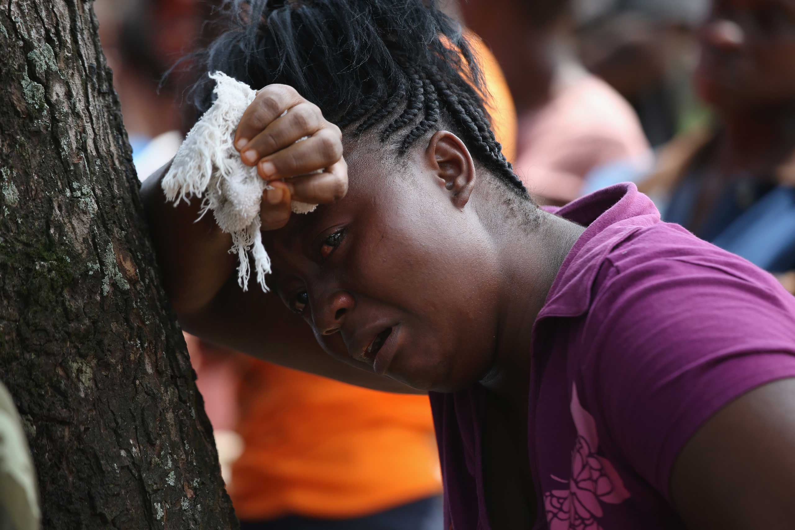 Korpo Klay watches as a Liberian health department burial team prepares to enter the home of her deceased cousin Kormassa Kaba, who was suspected of dying of the Ebola virus on Aug. 14, 2014 in Monrovia.