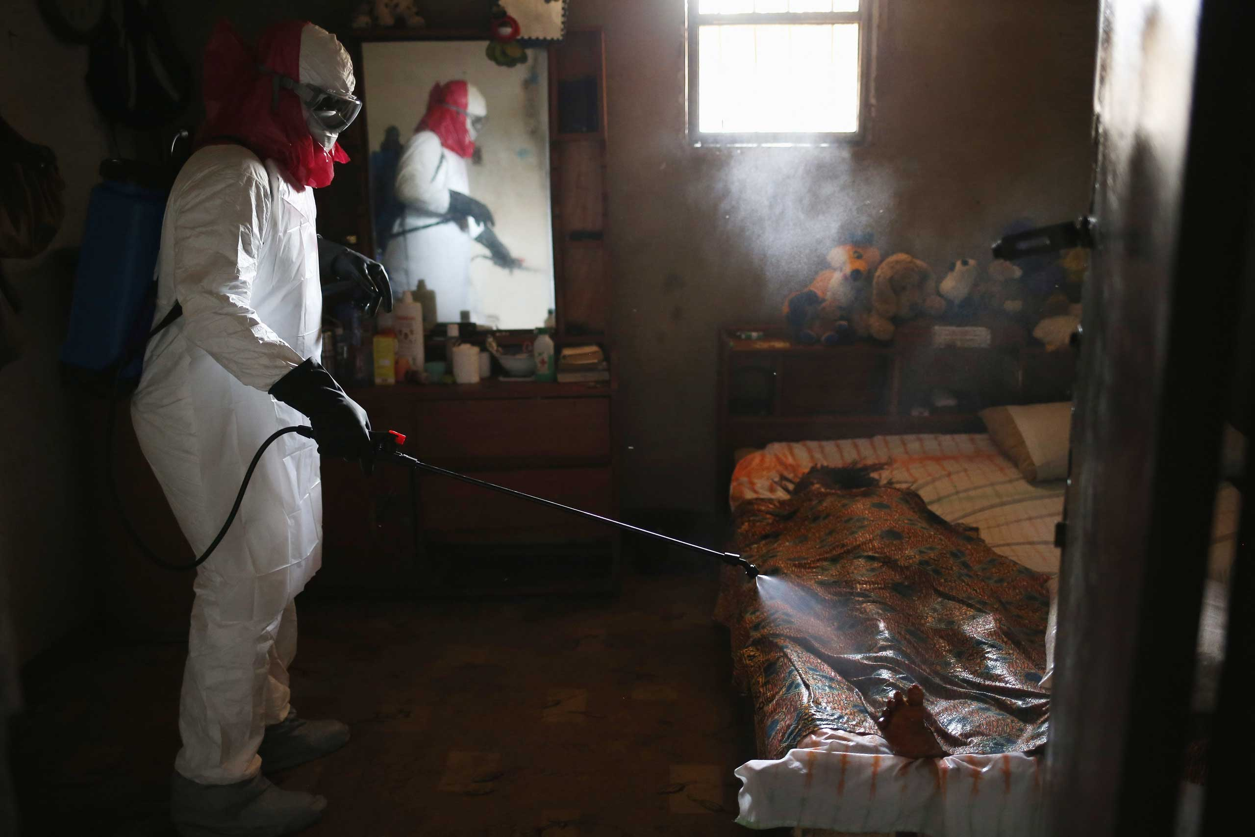 A burial team from the Liberian health department sprays disinfectant over the body of a woman suspected of dying of the Ebola virus on Aug. 14, 2014 in Monrovia.