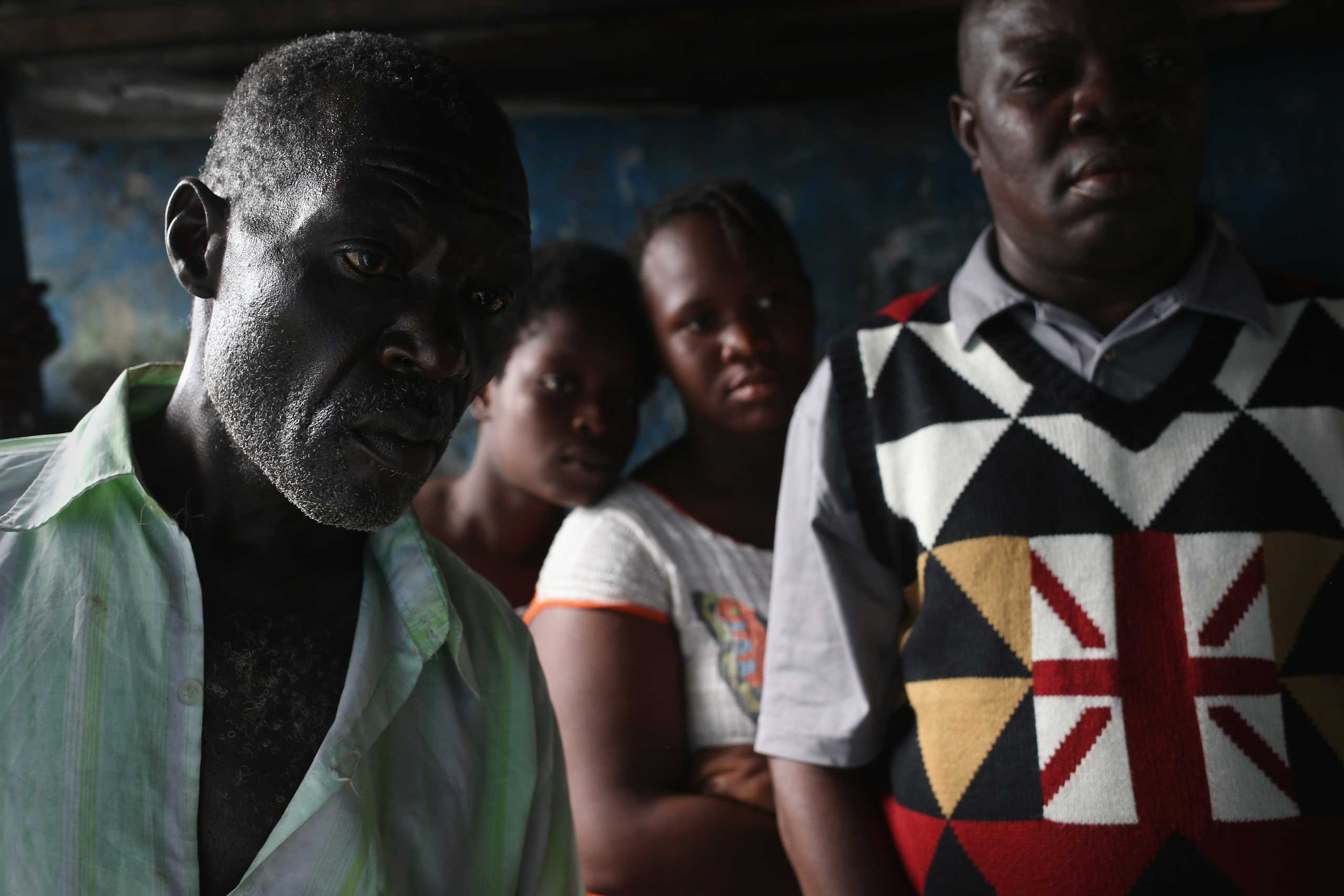 People watch as a son prepares his father to be taken to an Ebola isolation center on Aug. 15, 2014 in Monrovia.