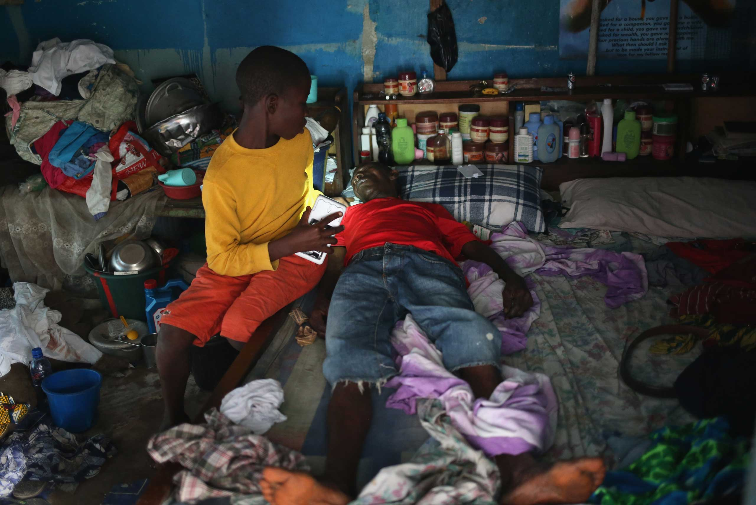 A son tries to prepare his father in their one-room home before they are taken to an Ebola isolation ward on Aug. 15, 2014 in Monrovia.