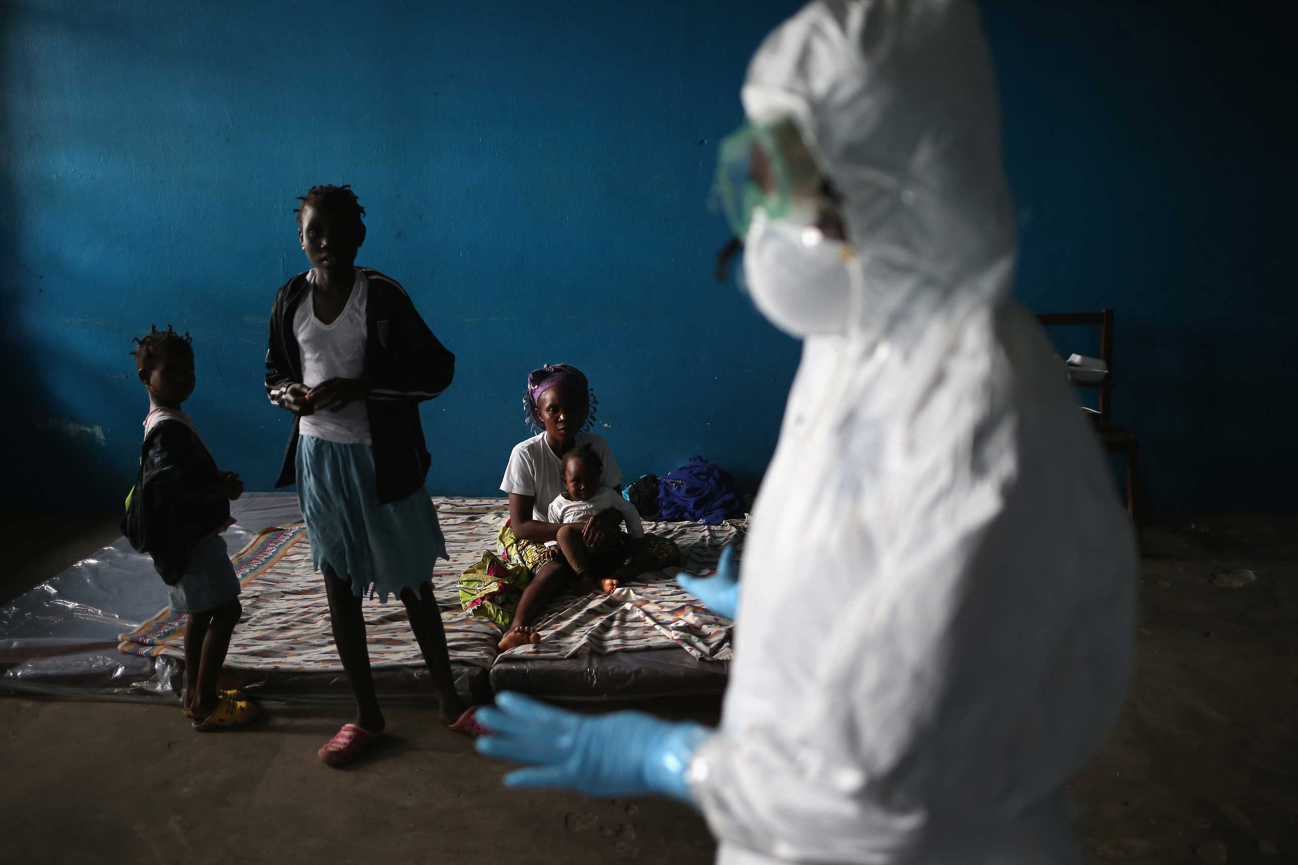 A Liberian health worker speaks with families in a classroom now used as Ebola isolation ward on Aug. 15, 2014 in Monrovia.