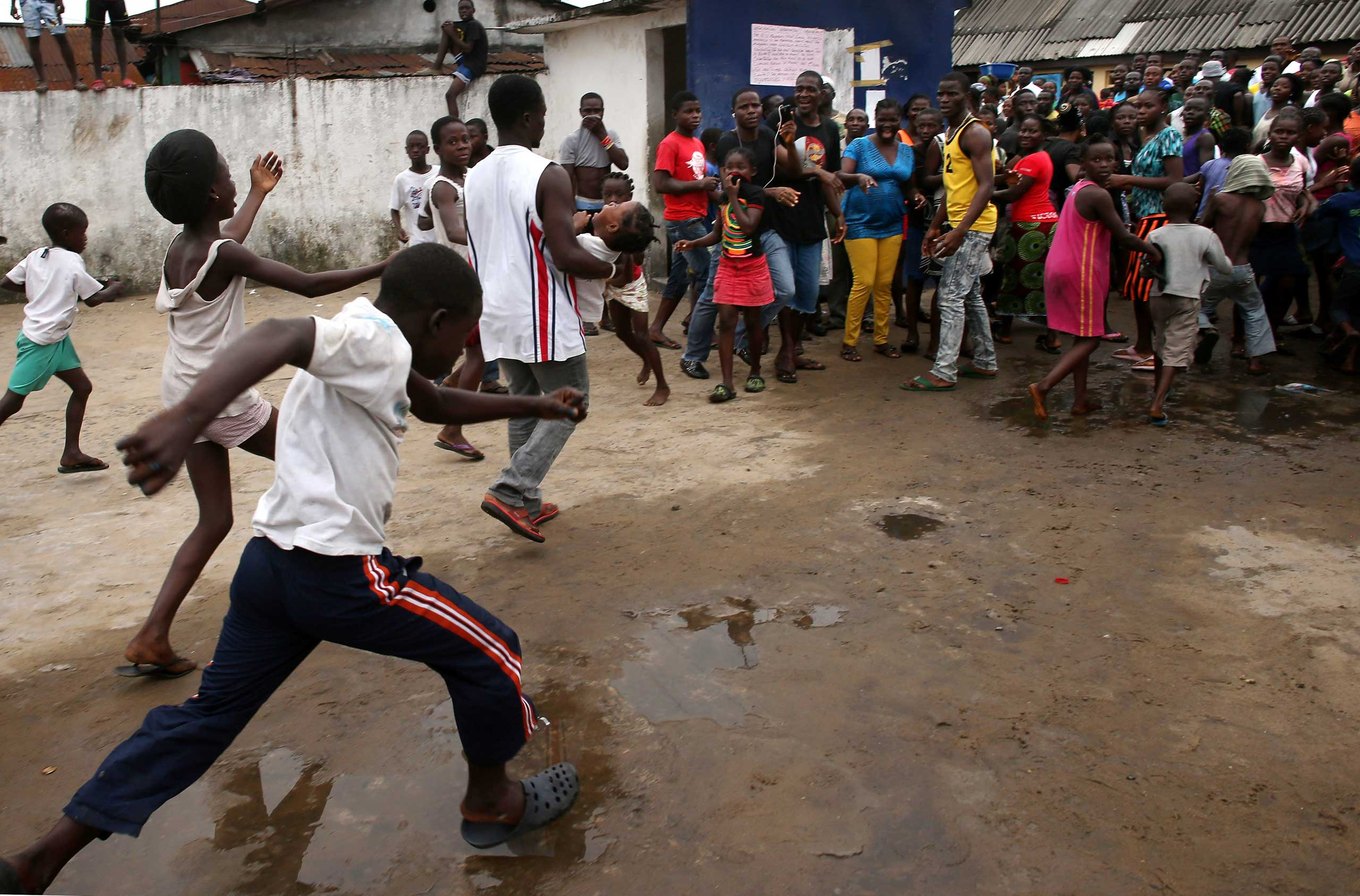 A man carries out a girl from an Ebola isolation center as a mob overruns the facility in the West Point slum on Aug. 16, 2014 in Monrovia.
