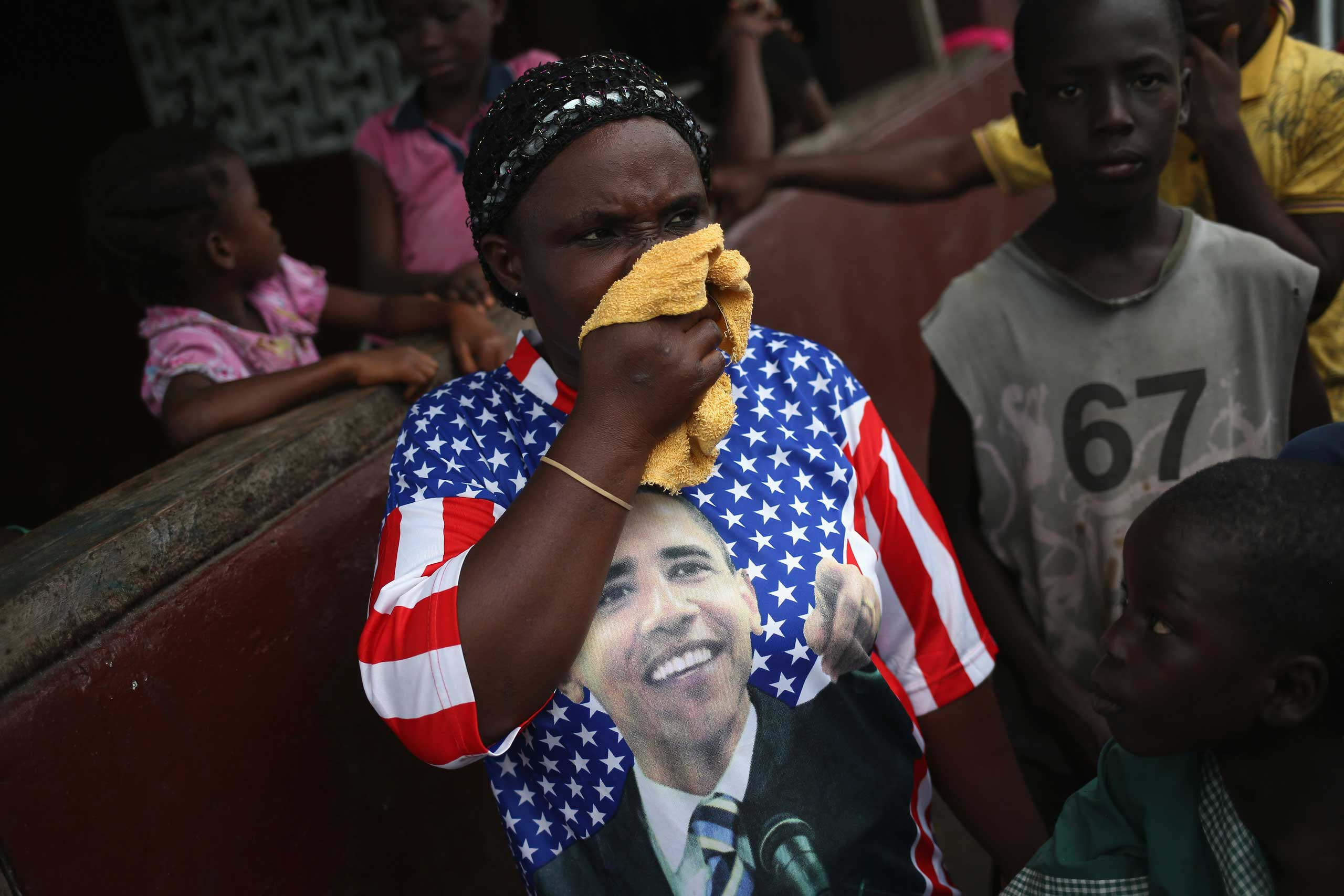 A woman wipes her nose after protesters drove out an Ebola burial team who had come to collect the bodies of four people who had died overnight in the West Point slum on Aug. 16, 2014 in Monrovia.
