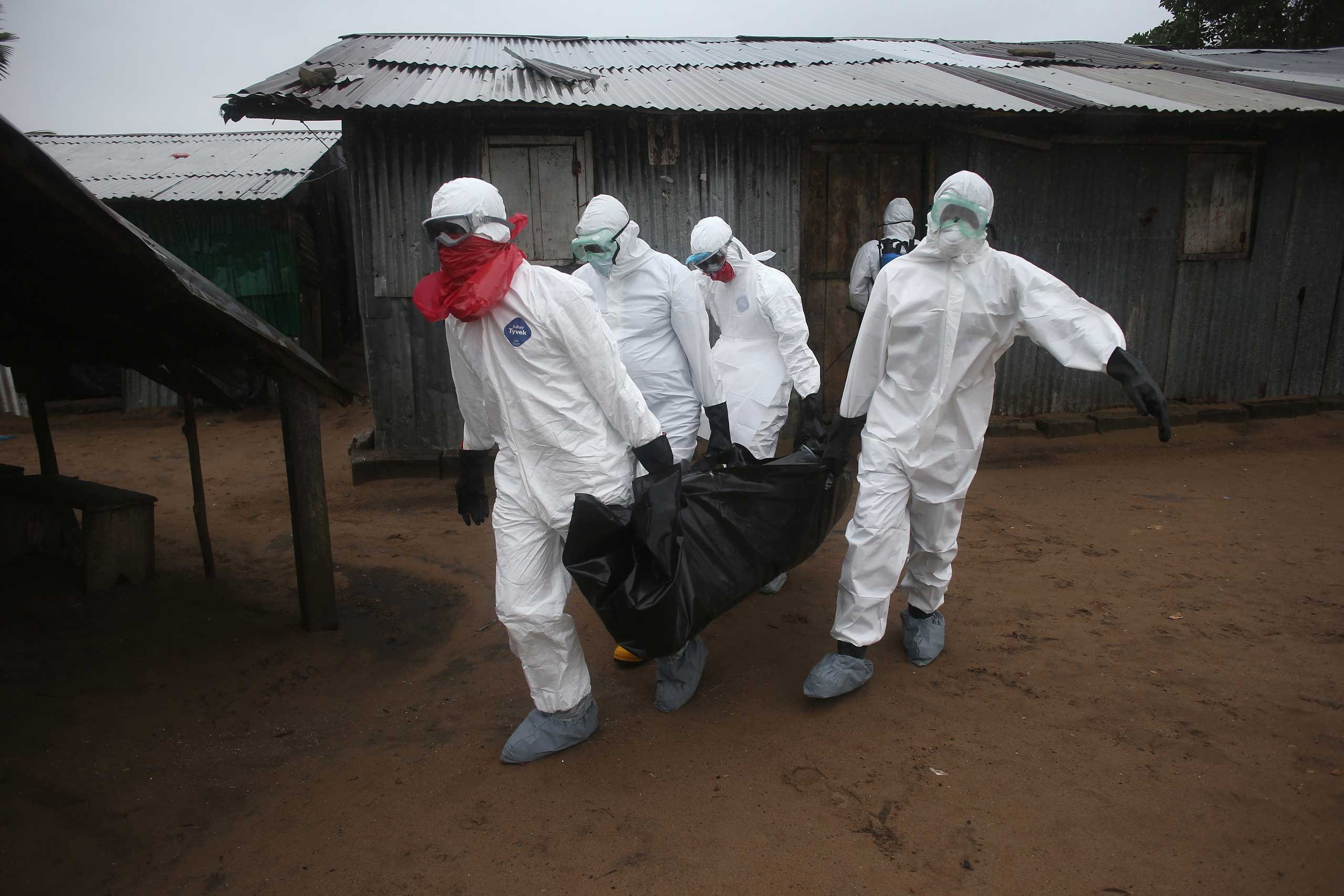 A Liberian burial team wearing protective clothing retrieves the body of a 60-year-old Ebola victim from his home on Aug. 17, 2014 near Monrovia.