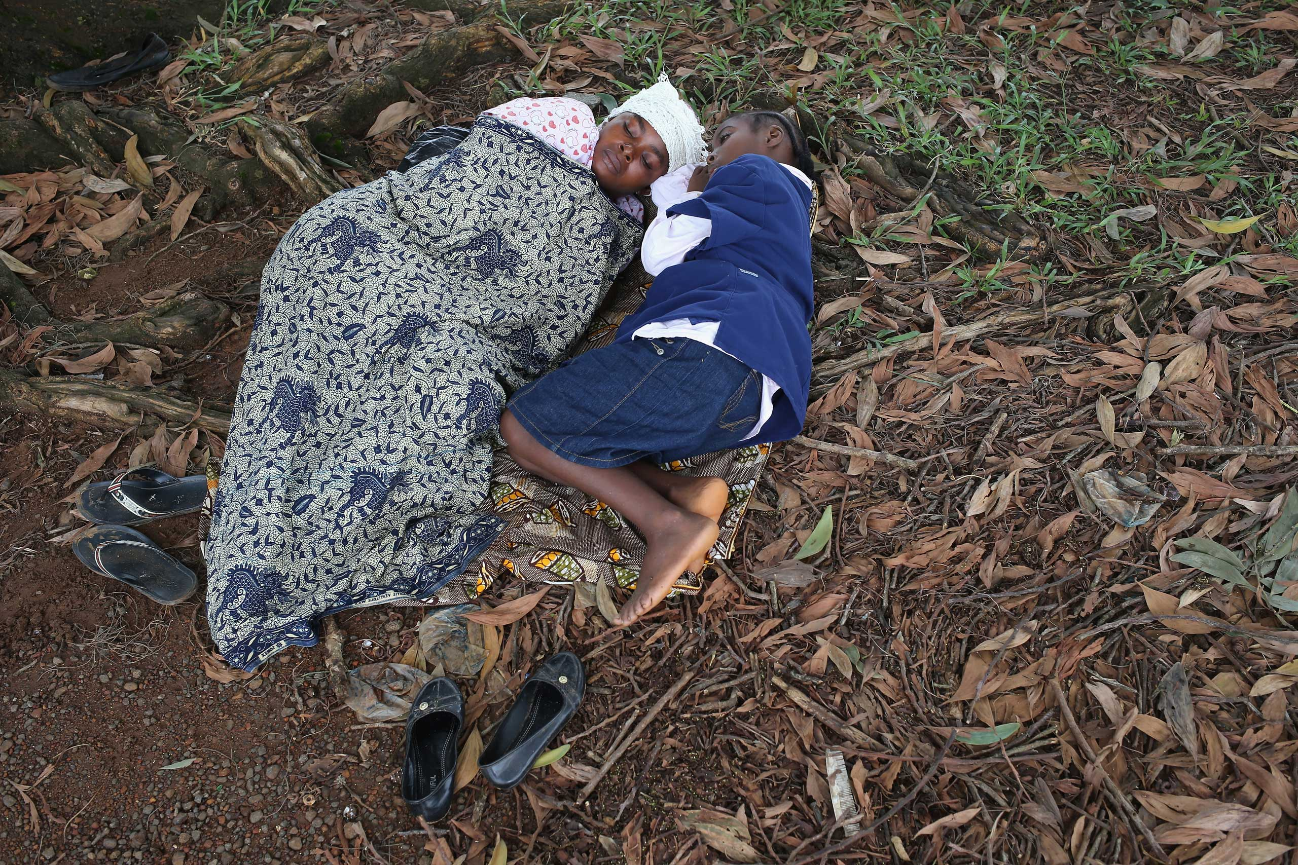 Hanah Siafa lies with her daughter Josephine, 10, while hoping to enter the new Doctors Without Borders , Ebola treatment center on Aug. 17, 2014 in Monrovia.