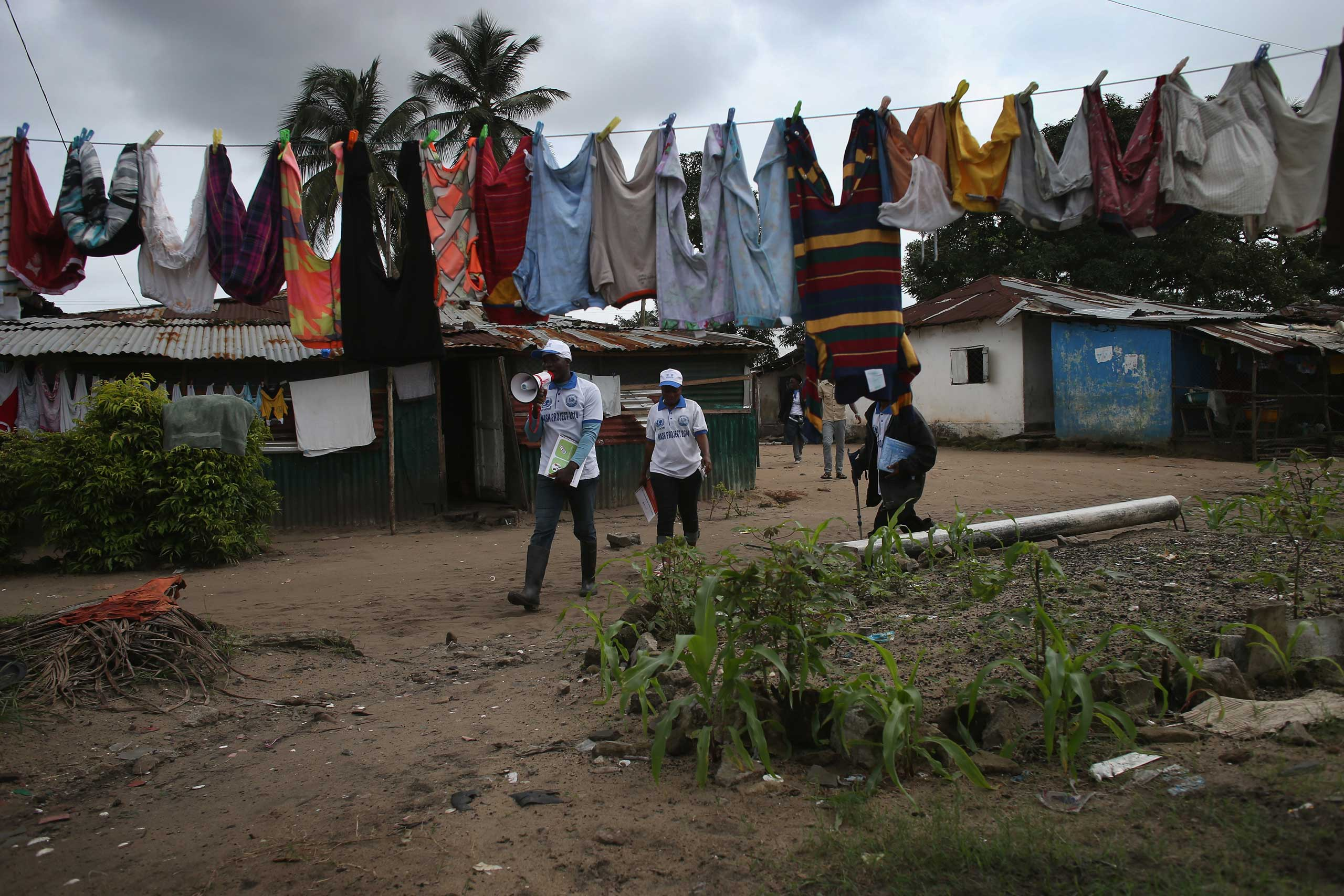 UNICEF health workers walk through the streets, going house to house to speak about Ebola prevention on Aug. 18, 2014 in New Kru Town.