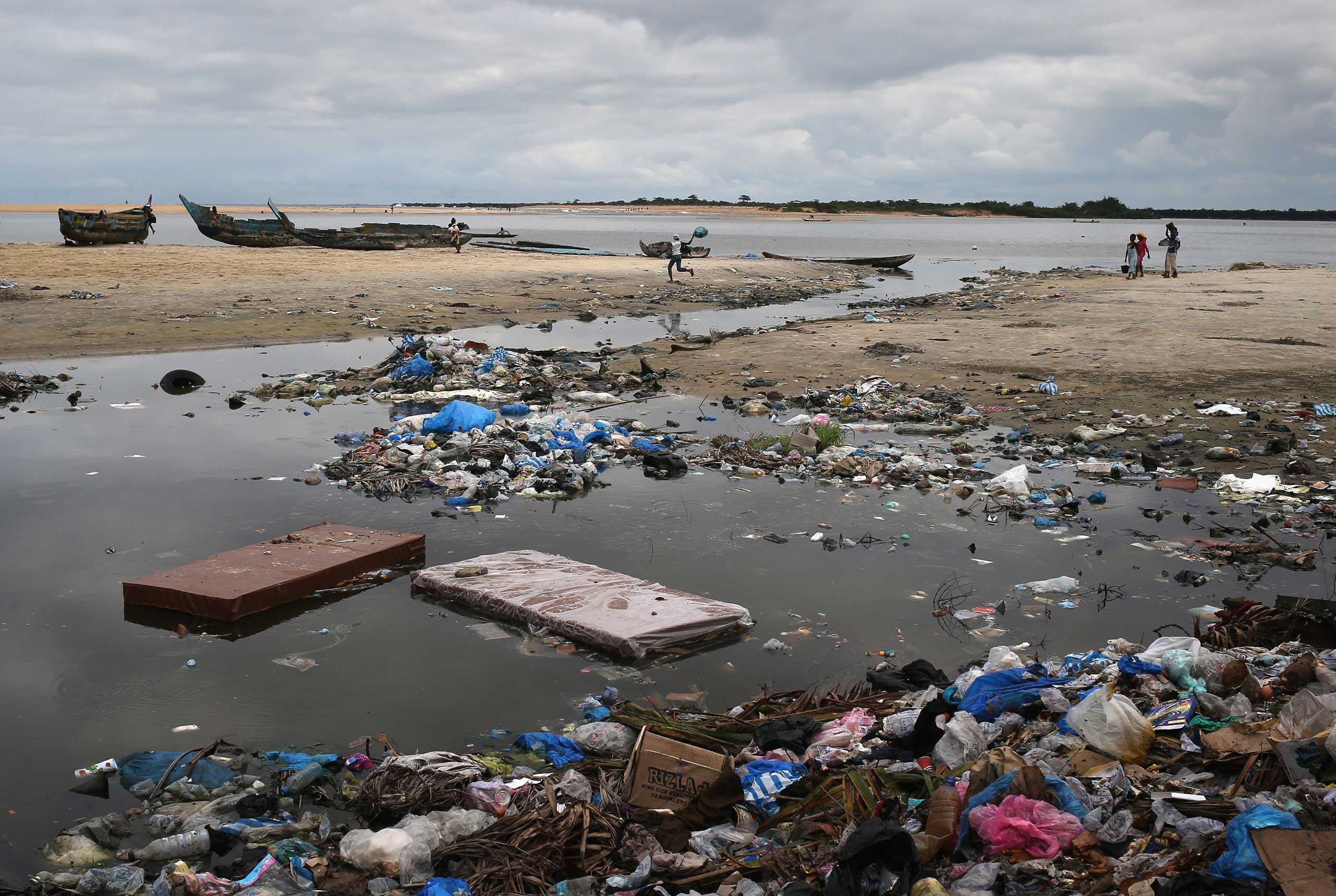 Mattresses that were looted from an isolation center for Ebola patients, local residents said, float in a seaside dump in the West Point slum in Monrovia on Aug. 19, 2014.