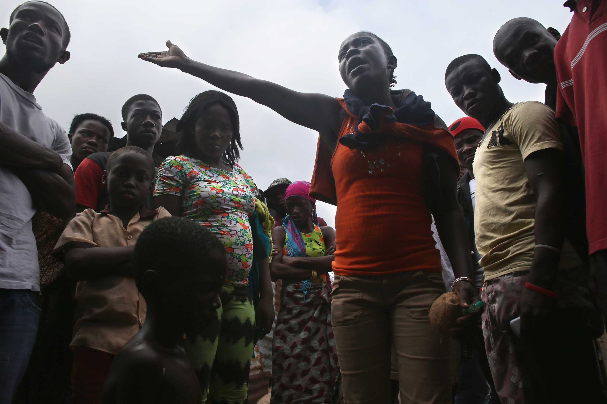 Local residents discuss how to help a very sick boy, 10, in a back alley of the West Point slum in Monrovia on Aug. 19, 2014. The boy was one of the patients who was pulled out of a holding center for suspected Ebola patients when the facility was overrun by a mob on Saturday.