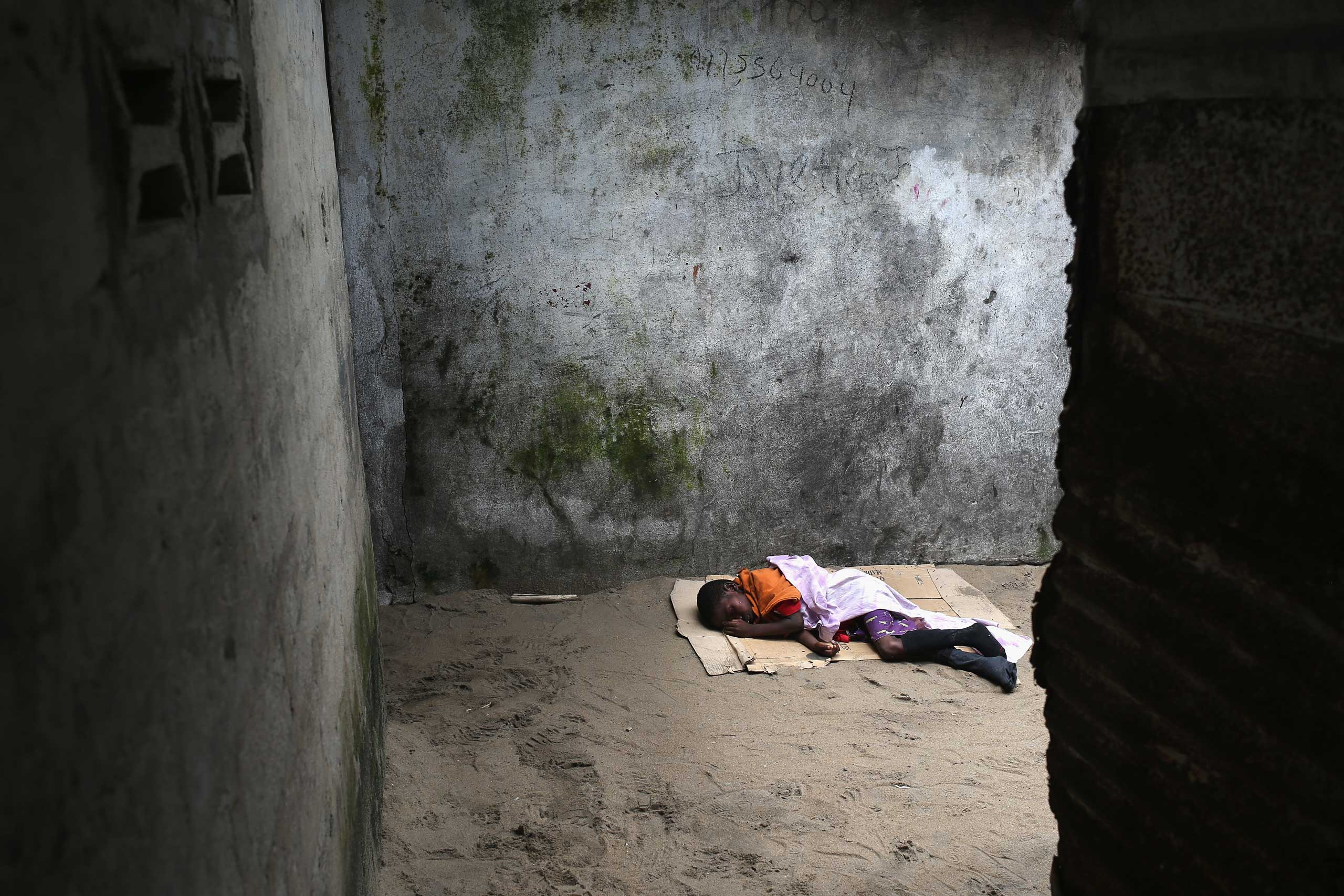A very sick boy, 10, lies in a back alley of the West Point slum in Monrovia on Aug. 19, 2014. The boy was one of the patients who was pulled out of a holding center for suspected Ebola patients when the facility was overrun by a mob on Saturday. A local clinic refused to treat the boy on Tuesday, according to residents, because of the danger of infection.
