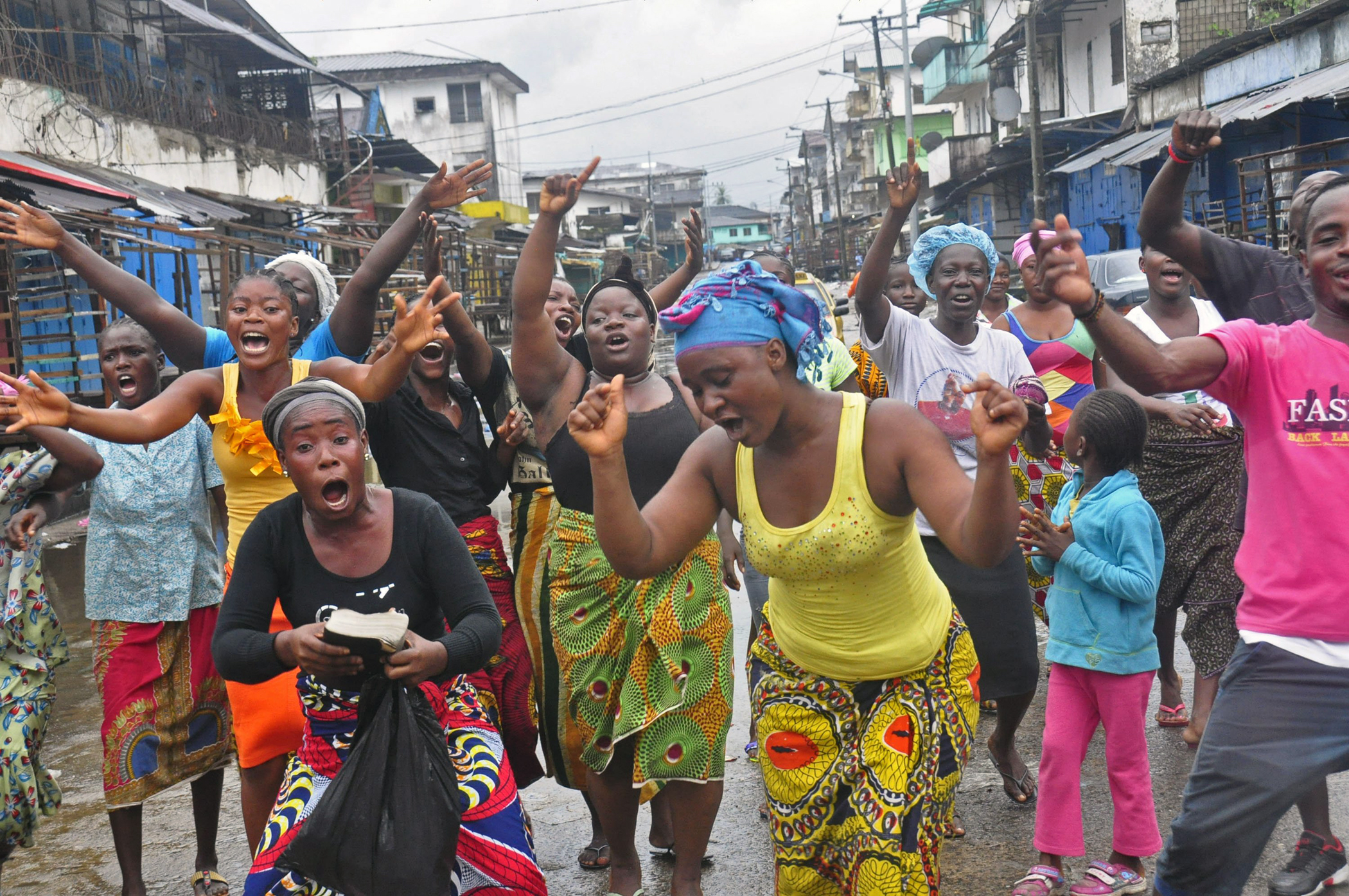 People celebrate in a street outside of West Point slum in Monrovia, Liberia, Aug. 30, 2014. Crowds cheer and celebrate in the streets after Liberian authorities reopened a slum where tens of thousands of people were barricaded amid the countryís Ebola outbreak.