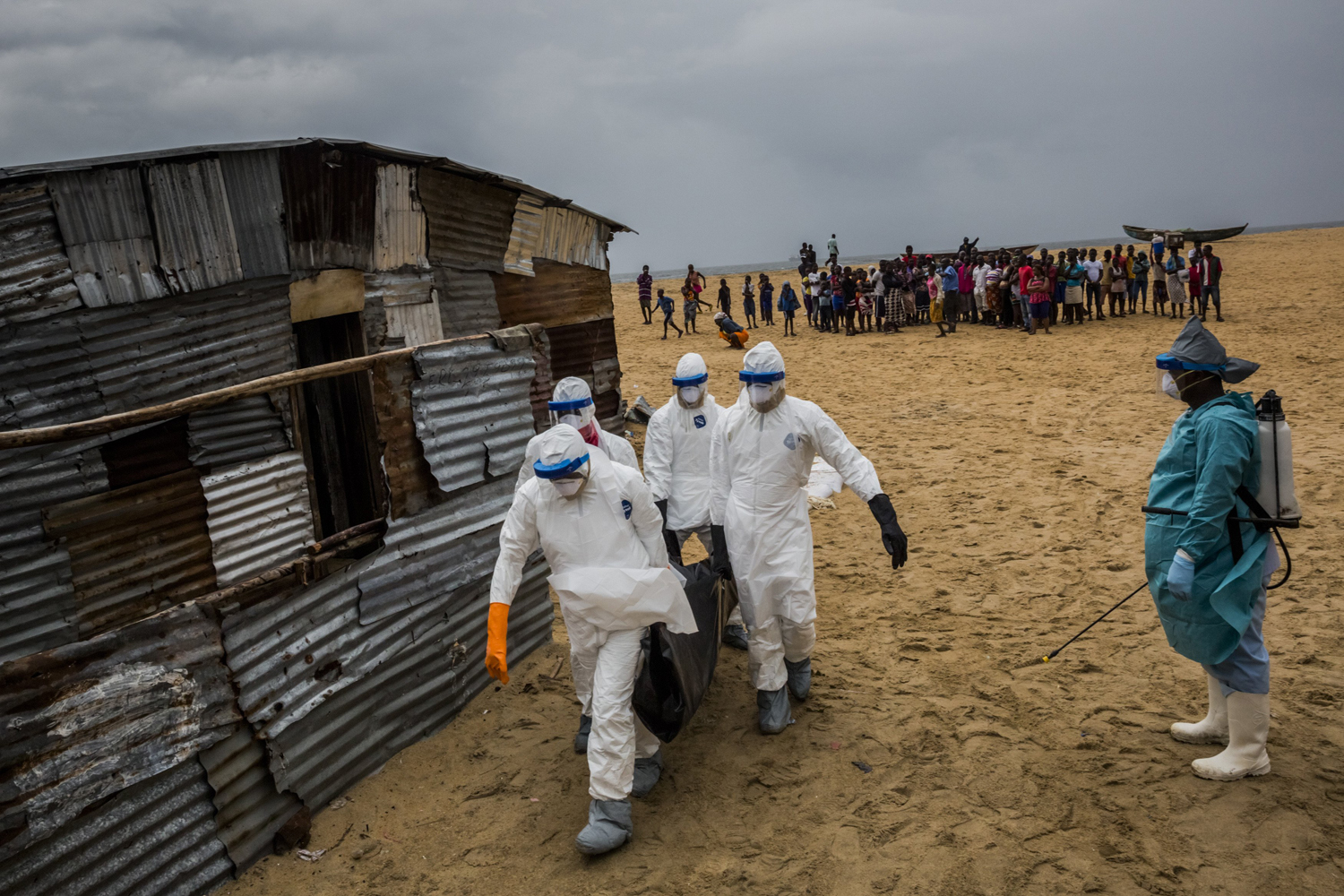 Liberian Red Cross burial team carry a body of a suspected Ebola victim from the West Point neighborhood in Monrovia, Liberia, Sept. 17, 2014.