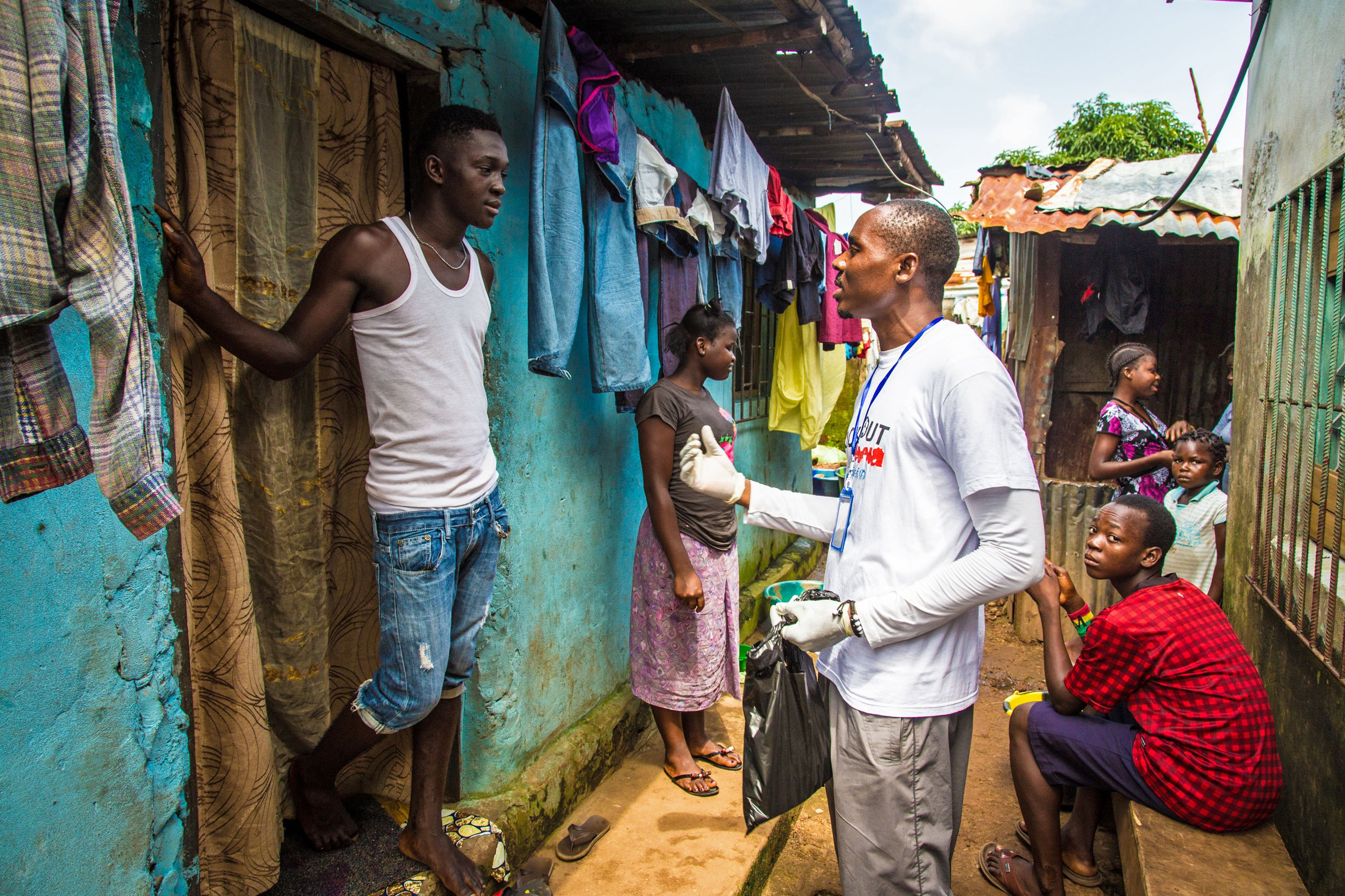 A volunteer health worker talks with a resident on how to prevent and identify the Ebola virus in others, and distributes bars of soap in Freetown, Sierra Leone, Sept. 20, 2014.