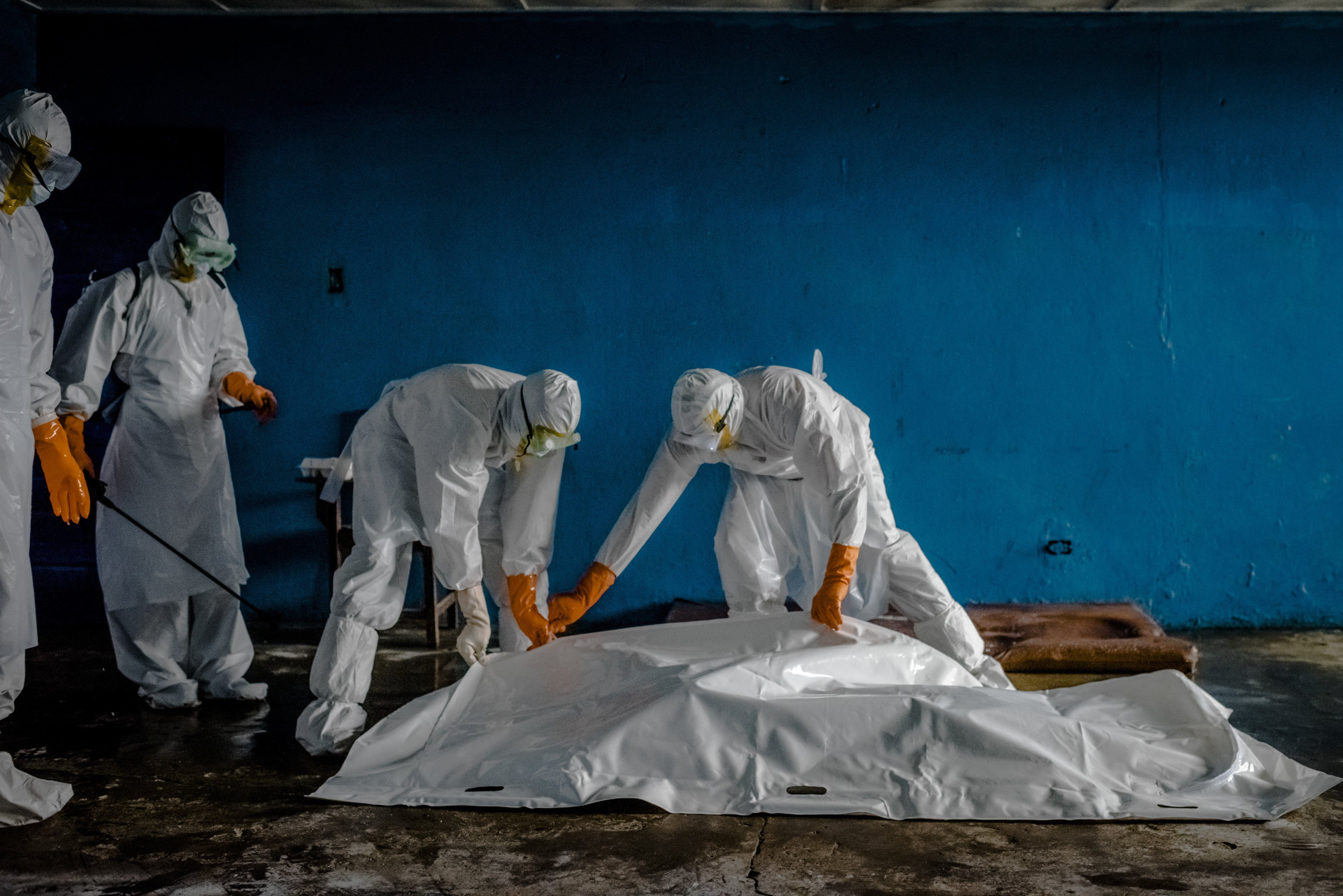 A burial team in protective clothing retrieves the body of an Ebola victim from an isolation ward in the West Point neighborhood of Monrovia, the capital of Liberia, on Aug. 28, 2014