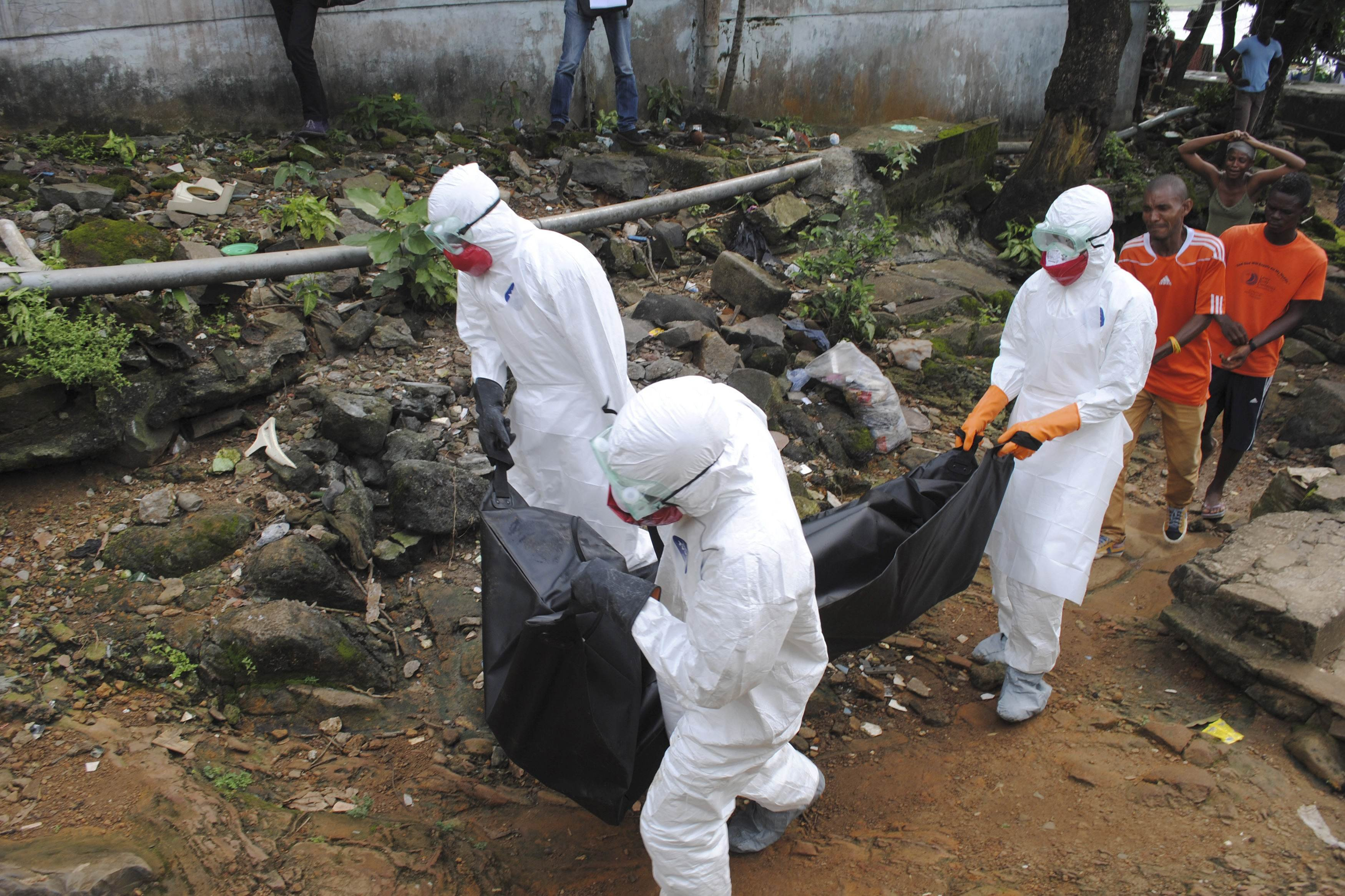 Health workers remove the body of Prince Nyentee, a 29-year-old man whom local residents said died of Ebola virus in Monrovia, Liberia on Sept. 11, 2014.