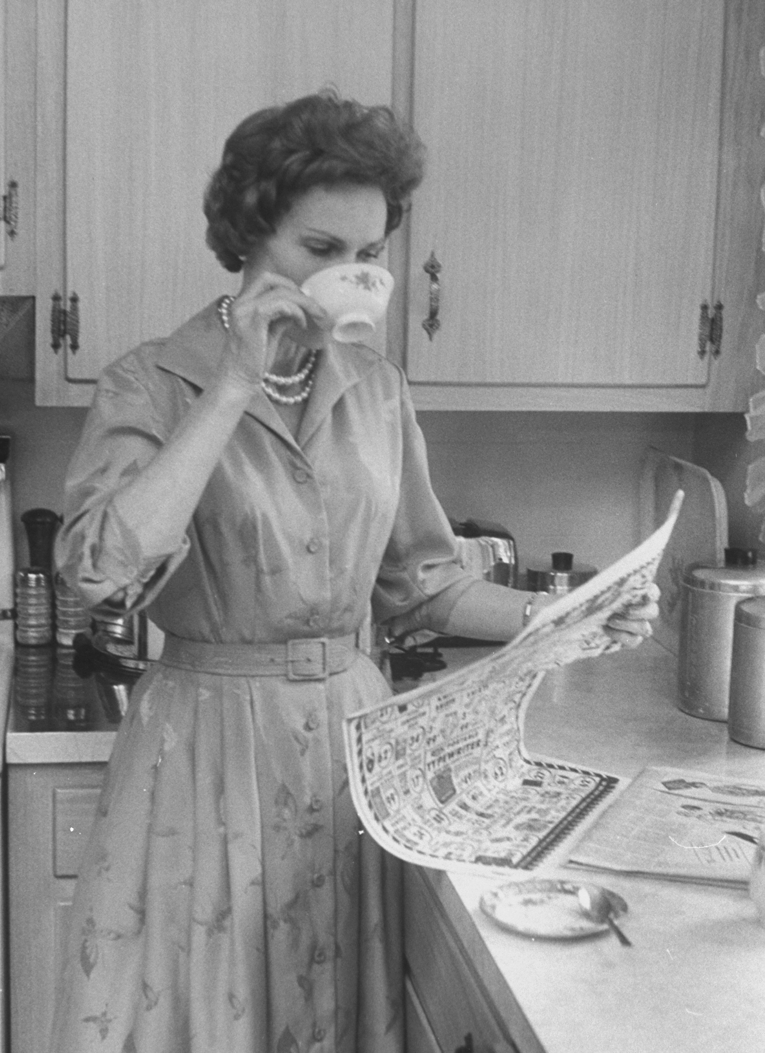 Mrs. Patricia Nixon at home reading the newspaper in Washington, 1960.