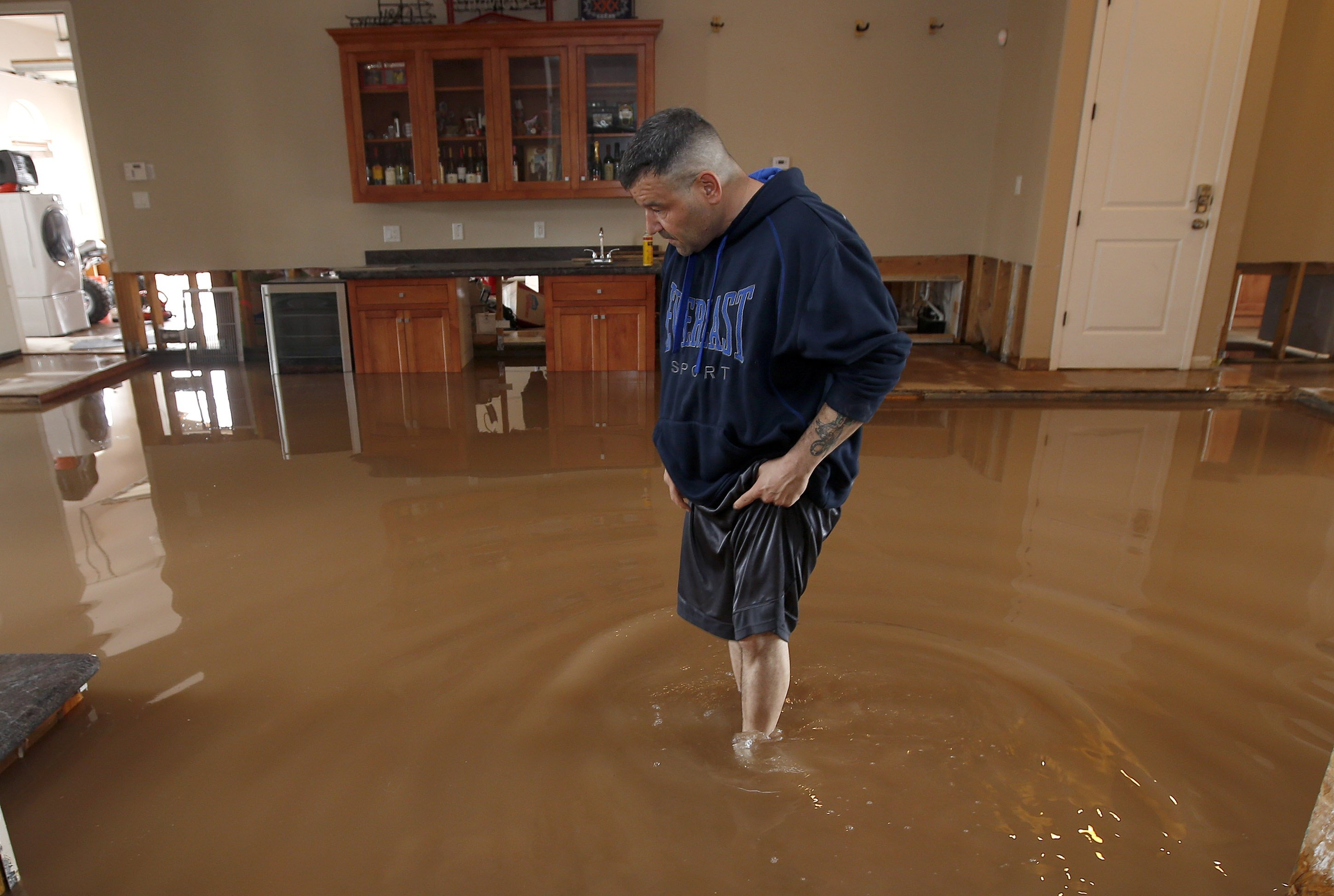 Nick Kriaris wades through his flooded home after heavy rains caused severe flash flooding in Phoenix on Sept. 8, 2014.