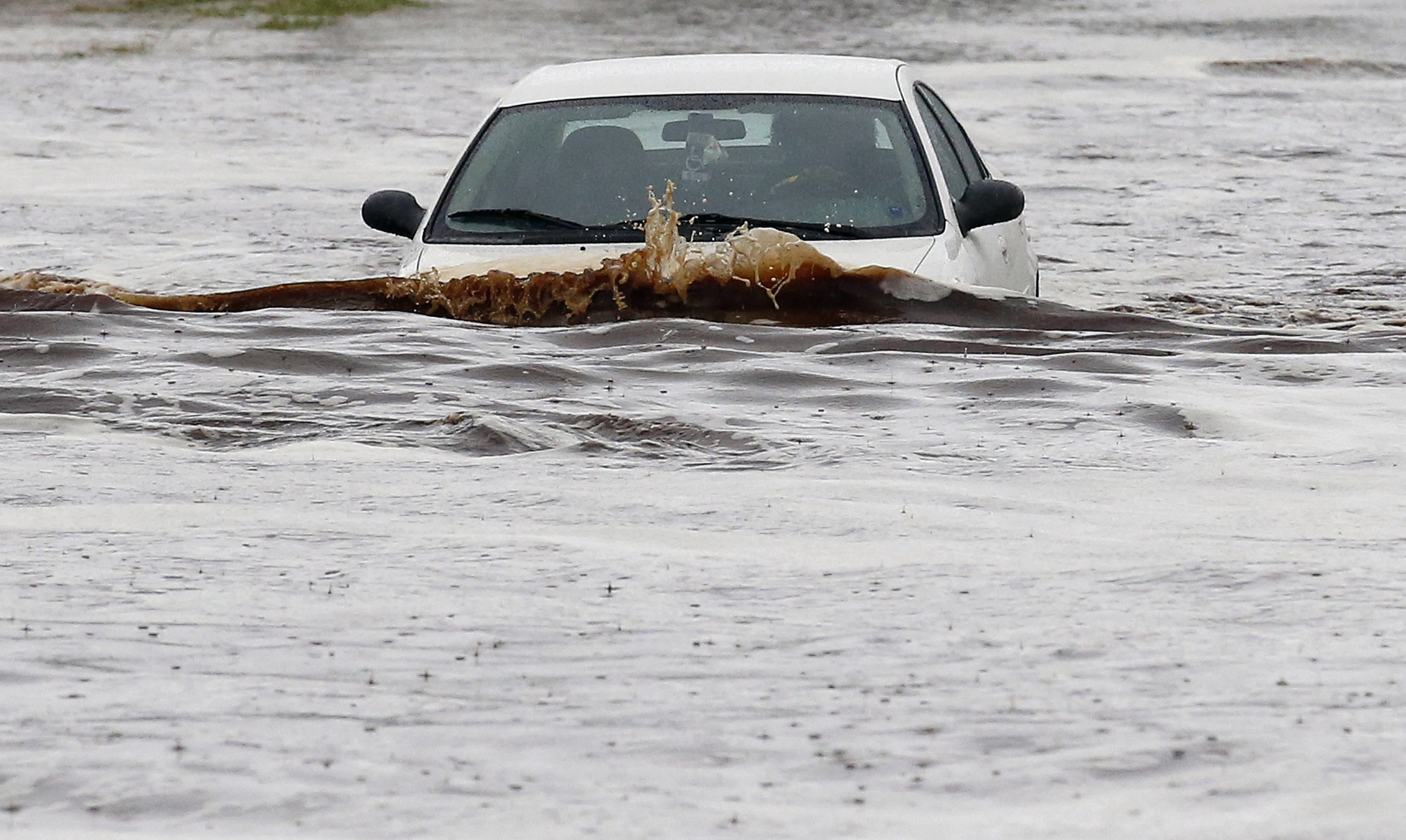 A driver tries to navigate a severely flooded street as heavy rains pour down in Phoenix, Sept. 8, 2014.