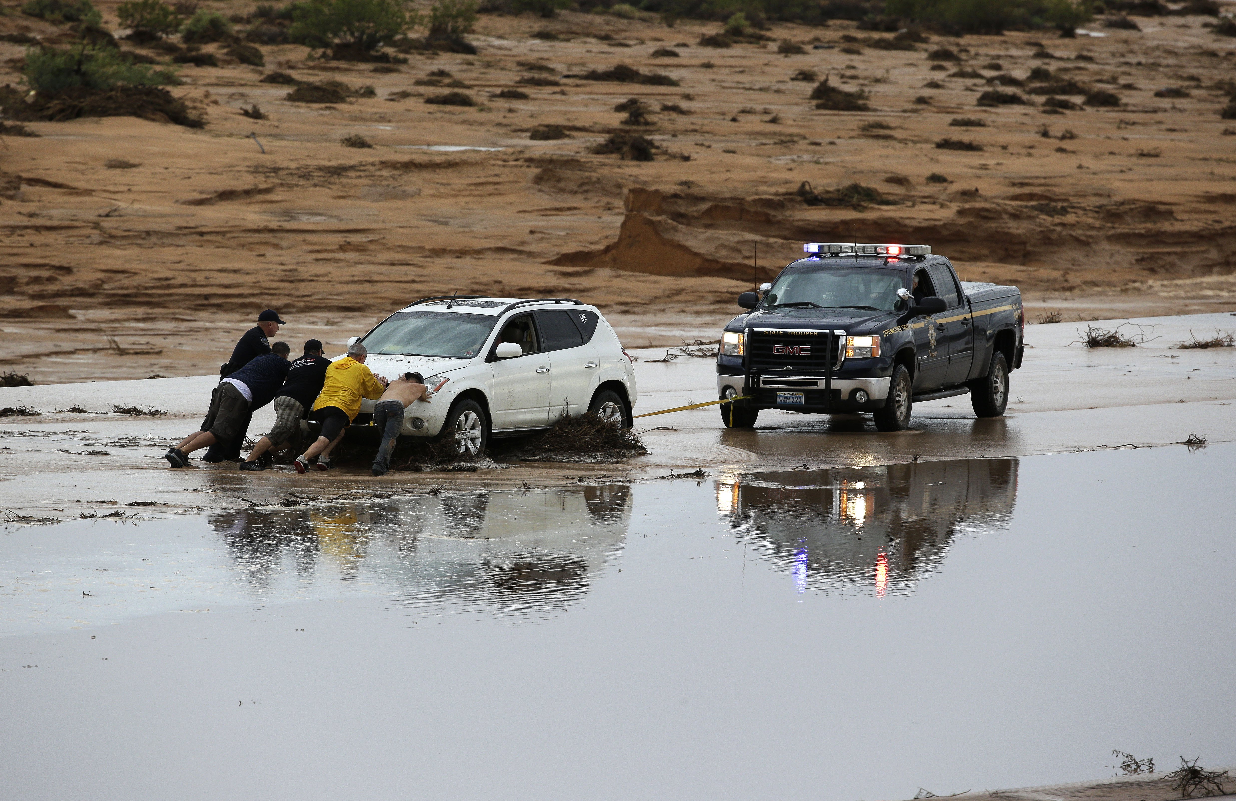 People try to free a car stuck in mud from flooding on Interstate 15 in Moapa, Nev., Sept. 8, 2014.