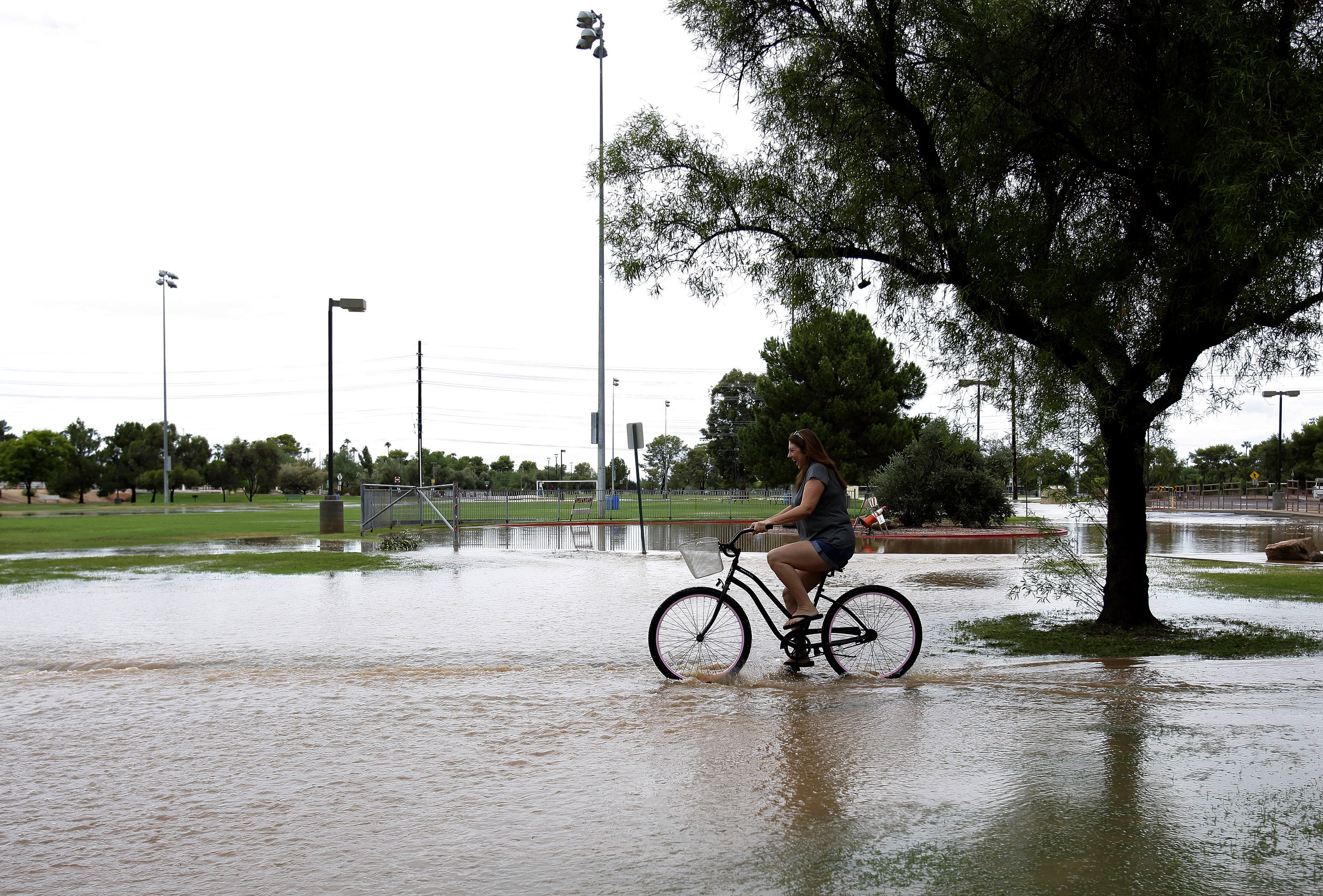 A woman rides her bike through a flooded pathway in Scottsdale, Ariz. on Sept. 8, 2014.