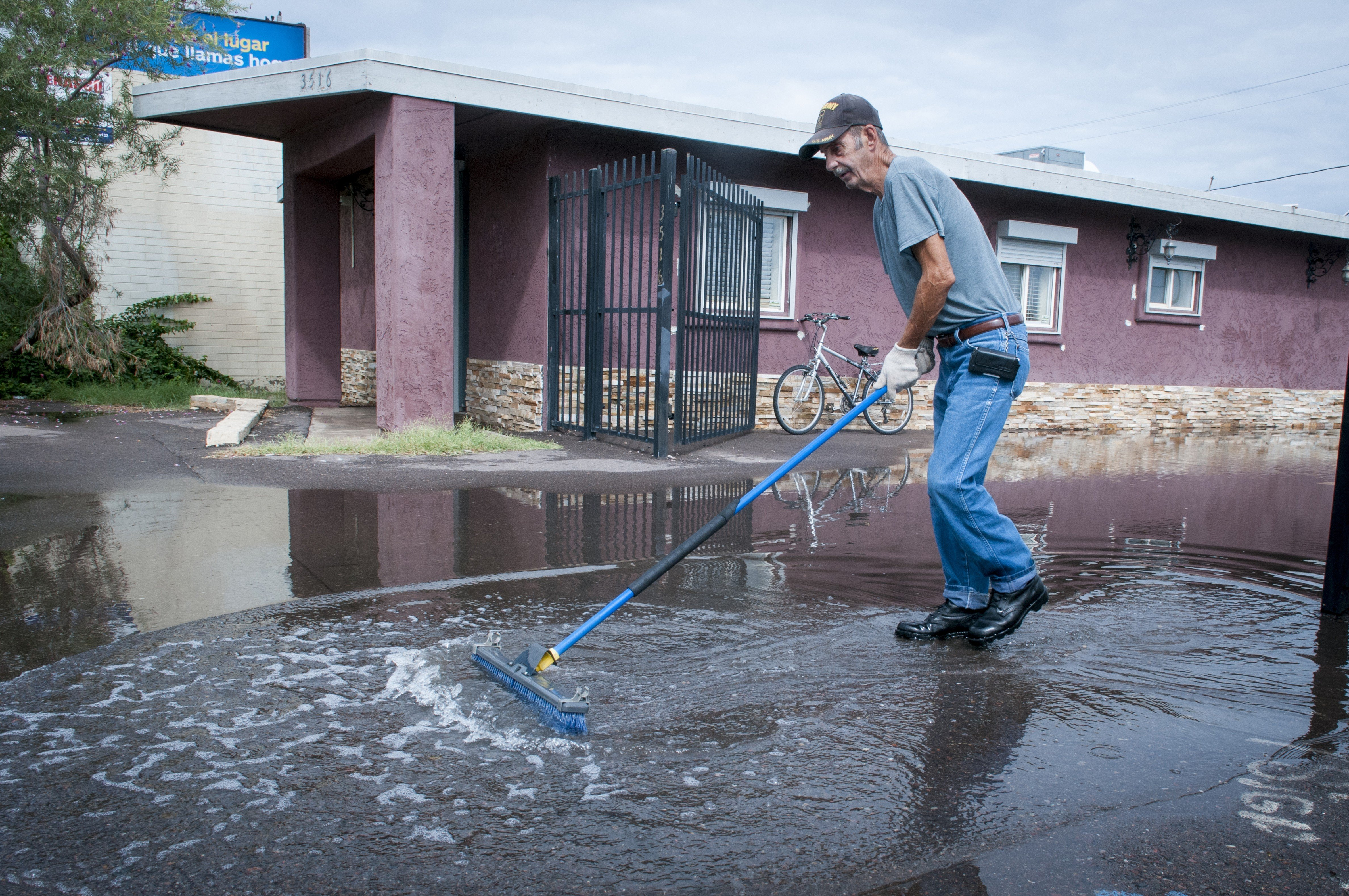 A Phoenix resident clears water from the flooded parking lot of a women's clinic on McDowell Rd. in Central Phoenix, Ariz. on Sept. 8, 2014.