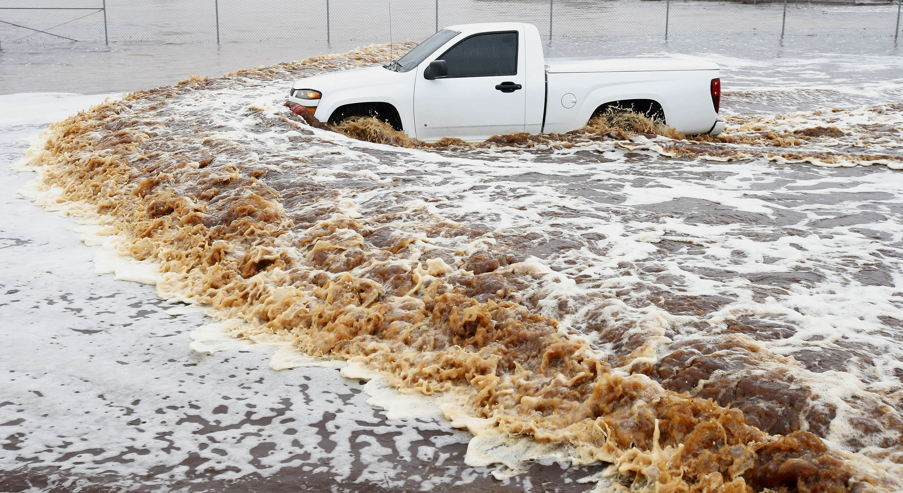 A truck creates a wake as its driver tries to navigate a severely flooded street as heavy rains pour down in Phoenix on Sept. 8, 2014.