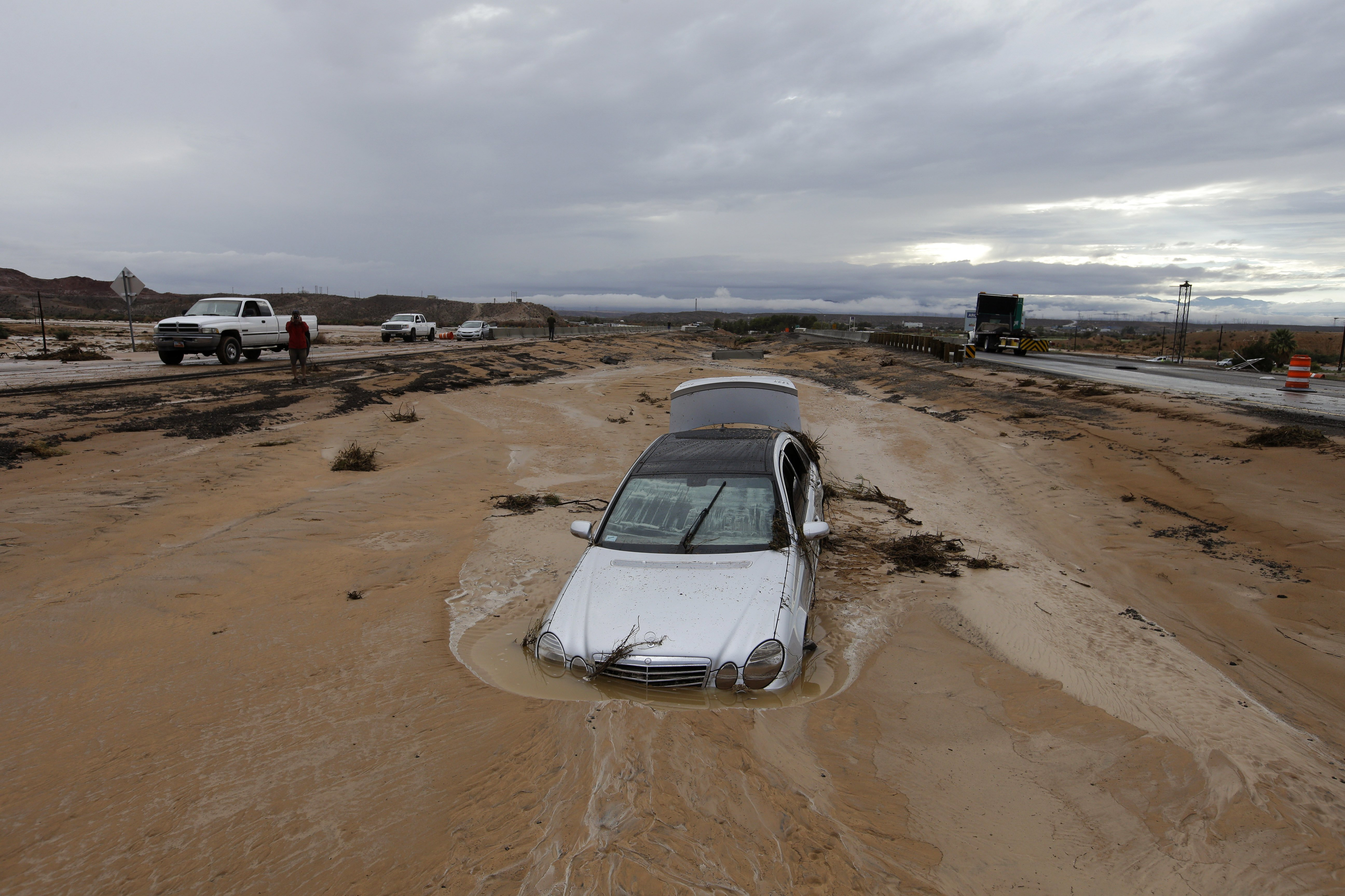A car is partially buried in mud on Interstate 15 in Moapa, Nev., Sept. 8, 2014.