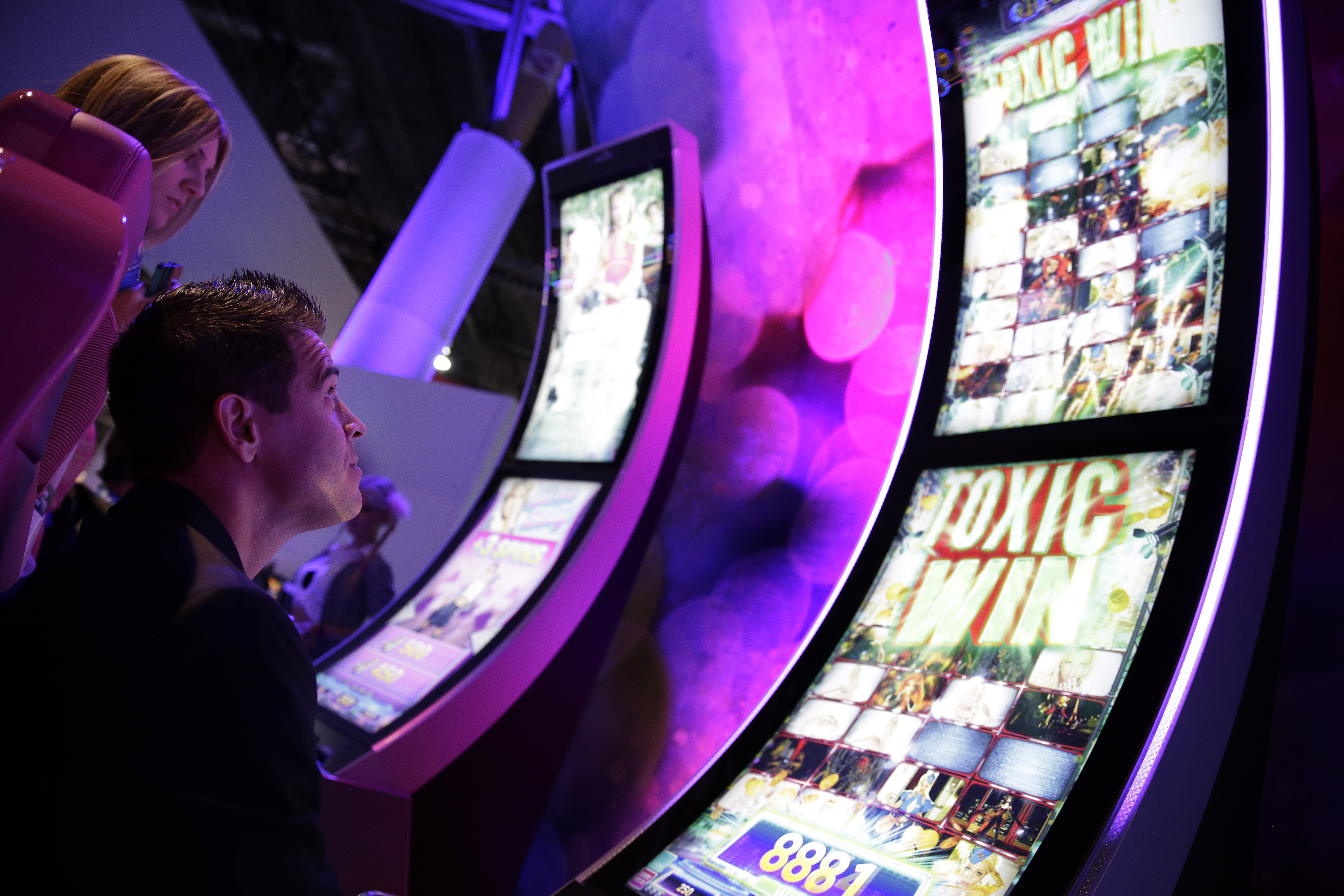 A man looks at a gambling machine at the Aristocrat booth during the Global Gaming Expo Tuesday, Sept. 30, 2014, in Las Vegas.