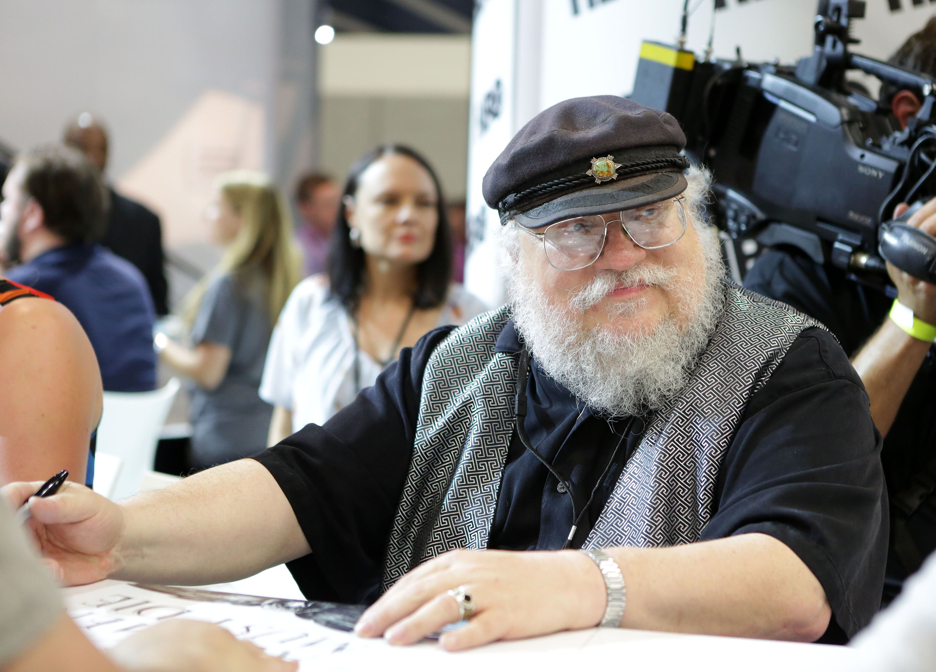 George R.R. Martin signs autographs during the 2014 Comic-Con International Convention.