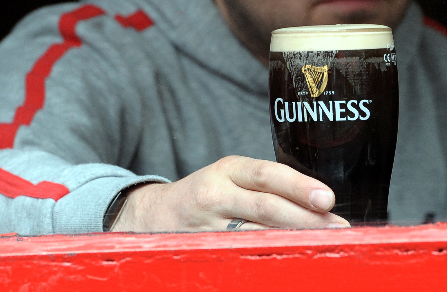 A man is pictured through the window of a bar drinking a pint of Guinness in The Temple Bar area of Dublin, Ireland on May 20, 2011.