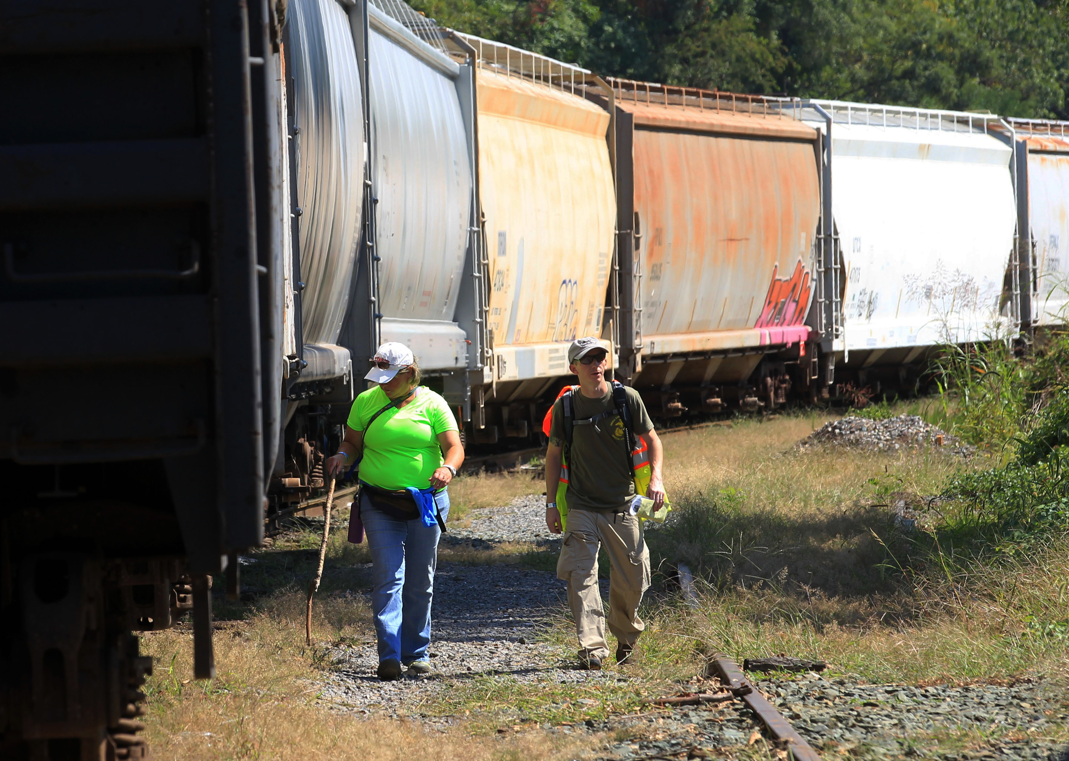 Volunteer Linda Cassell, left, walks with search team leader Brian Pace, as they search along the railroad tracks behind the Charlottesville Downtown Mall during a massive search effort by the community for missing University of Virginia student Hannah Graham, Sept. 20, 2014, in Charlottesville, Va.