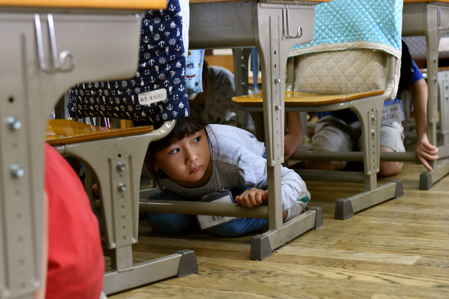 Sept. 1, 2014. Elementary school children take cover under their desks during an earthquake drill at a school in Tokyo on. Nationwide anti-disaster drills were held on September 1 on the anniversary of the massive 1923 earthquake which killed more than 140,000 people in the Tokyo metropolitan area.
